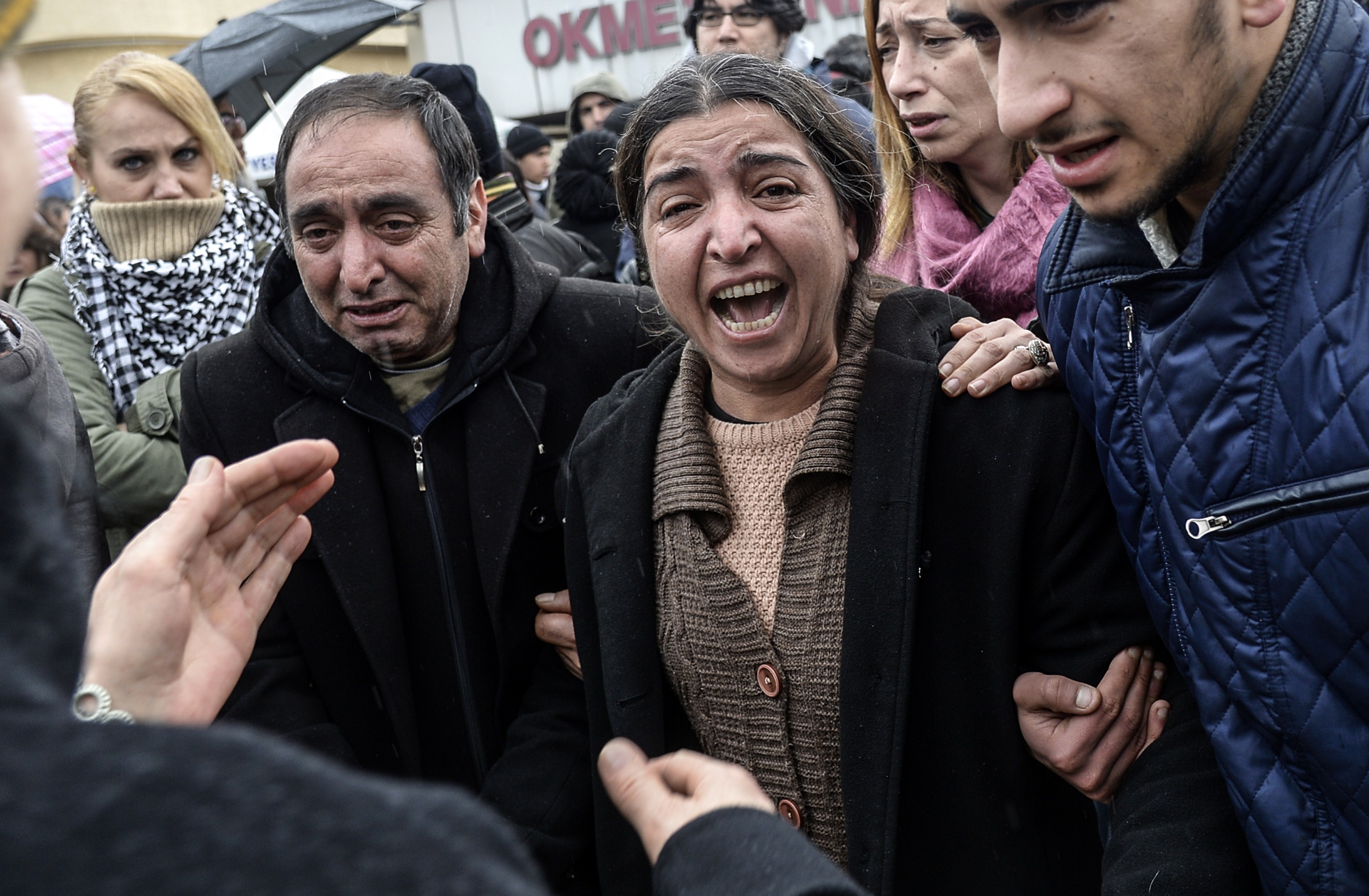 The mother (C) of 15-year-old Berkin Elvan cries after her son died at Okmeydani Hospital in Istanbul on March 11, 2014. Violent protests erupted between Turkish police and hundreds of protesters outside the hospital where the teenager, who had fallen into a coma after being hit by a tear gas canister during mass anti-government protests last year, died.  (AFP PHOTO/BULENT KILIC)