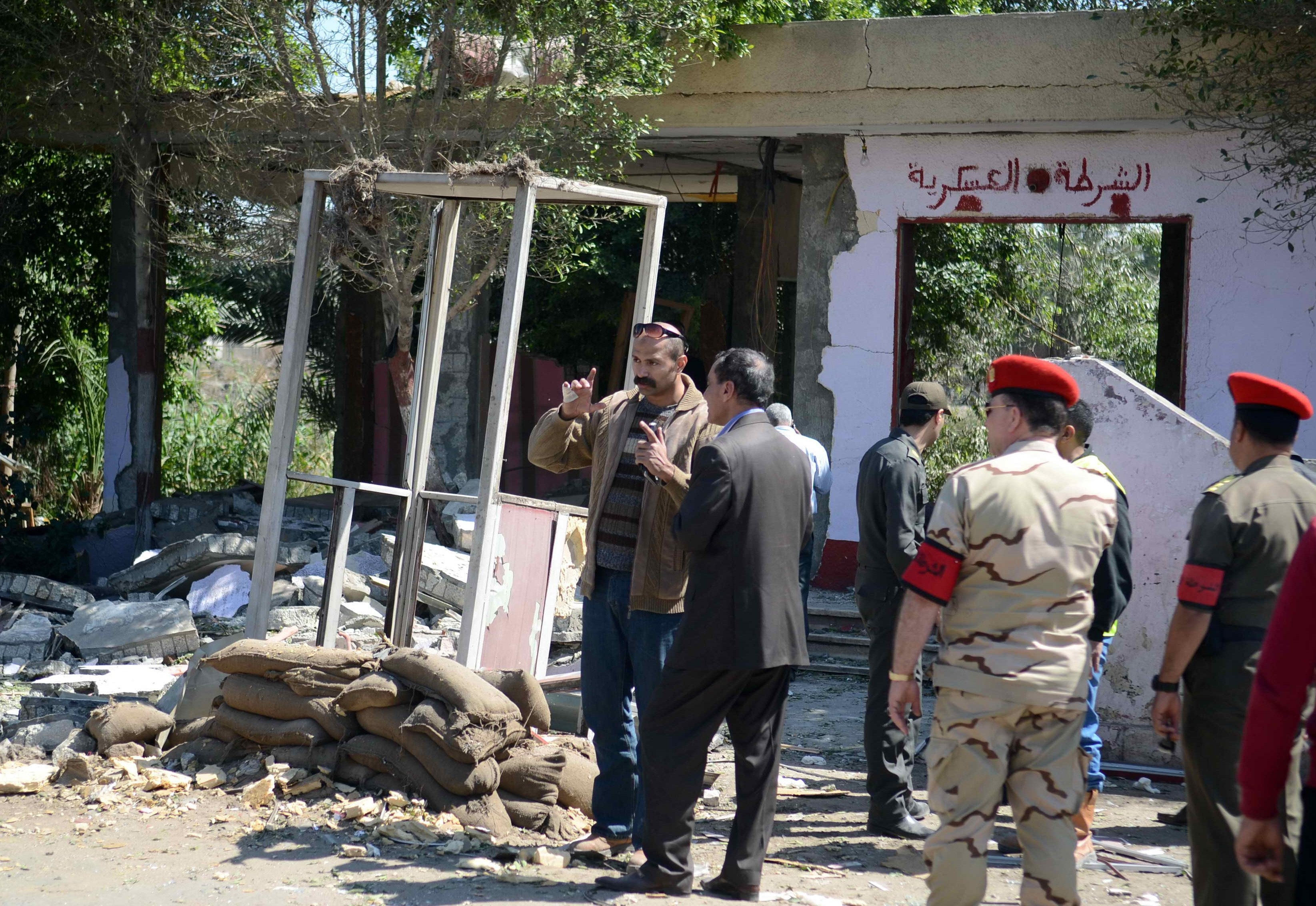 Egyptian soldiers and officials inspect the sight where gunmen killed six soldiers at a Cairo checkpoint on March 15, 2014  in an attack the military blamed on the Muslim Brotherhood movement of deposed president Mohamed Morsi. The attack came two days after gunmen killed a soldier in Cairo, as militants once based in the Sinai Peninsula increasingly target the capital in a campaign that has killed more than 200 security men since the army overthrew Morsi last July.  (AFP PHOTO / AHMED GAMEL)