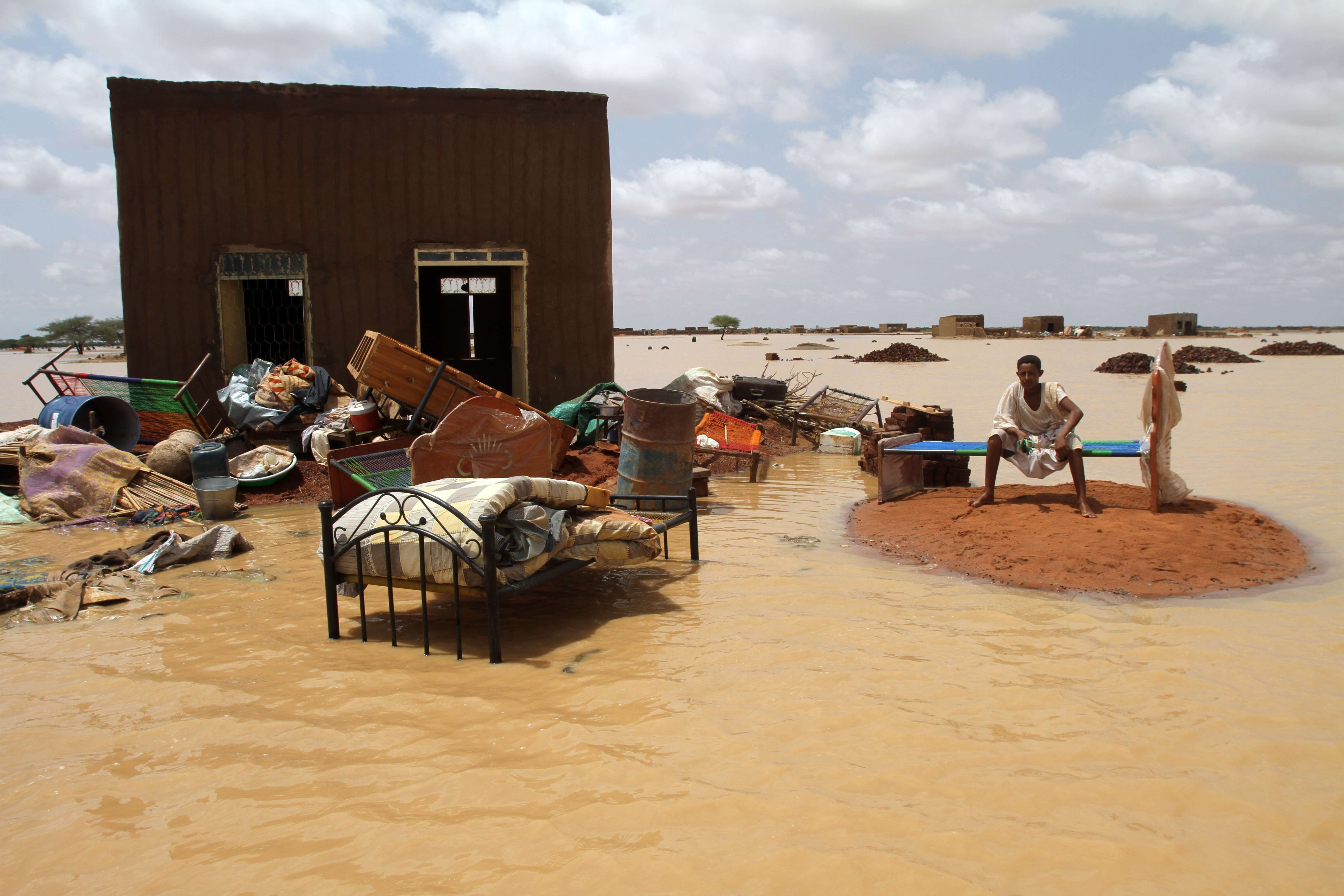 Sudanese man sits next to his house in a flooded street on the outskirts of the capital Khartoum on August 10, 2013. Drainage is poor in the capital, where even a little rain can cause flooding but this year's water surge was unusually severe. AFP PHOTO / ASHRAF SHAZLY