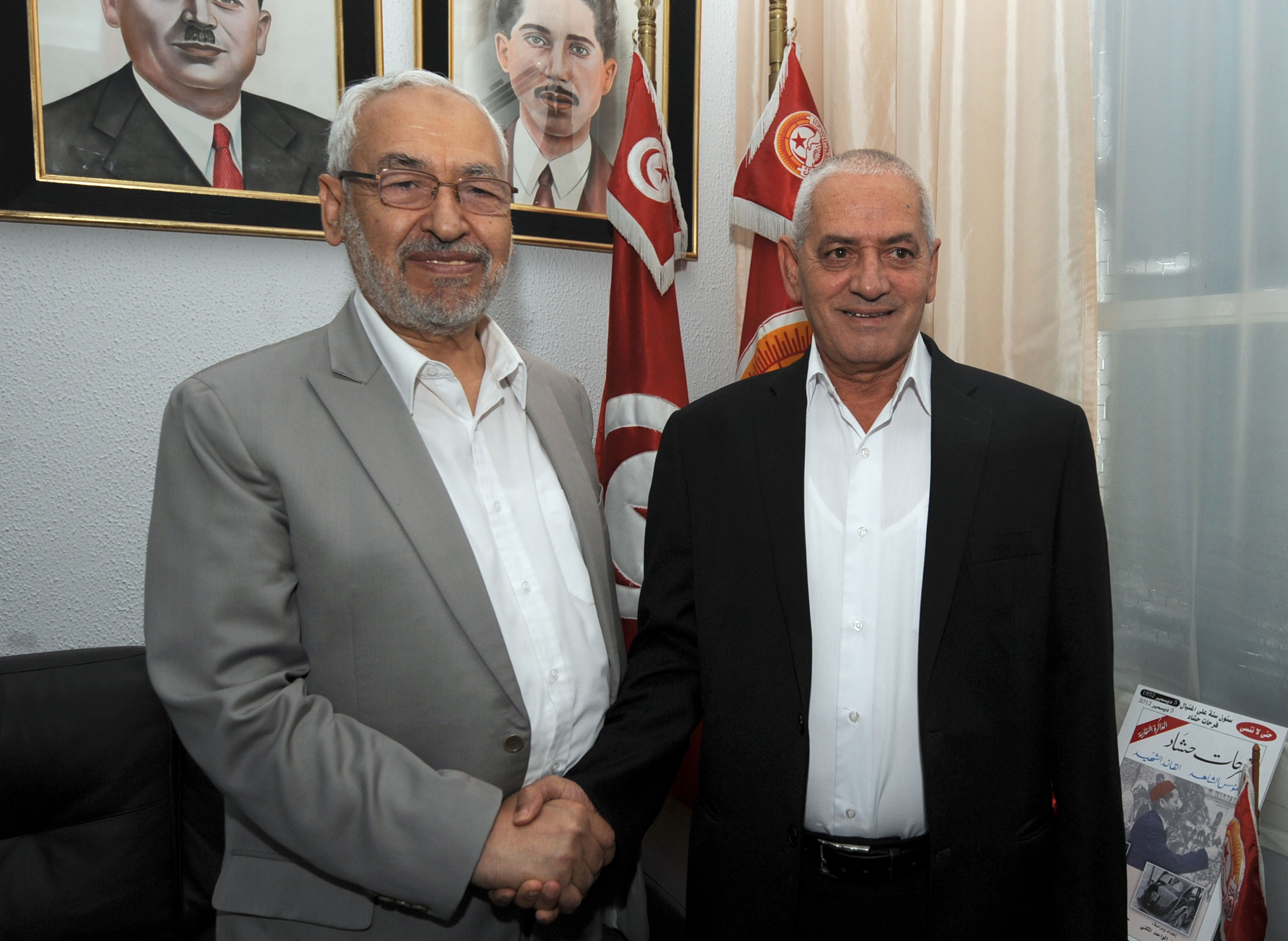 Leader of the ruling Ennahdha Islamist party Rached Ghannouchi (L) shakes hands with Secretary General of the Tunisian General Labour Union (UGTT) Houcine Abbassi, during a meeting in Tunis on August 12, 2013. The two leaders met to discuss the political crisis in Tunisia sparked by the murder of opposition politician Mohamed Brahmi in July. AFP PHOTO / FETHI BELAID