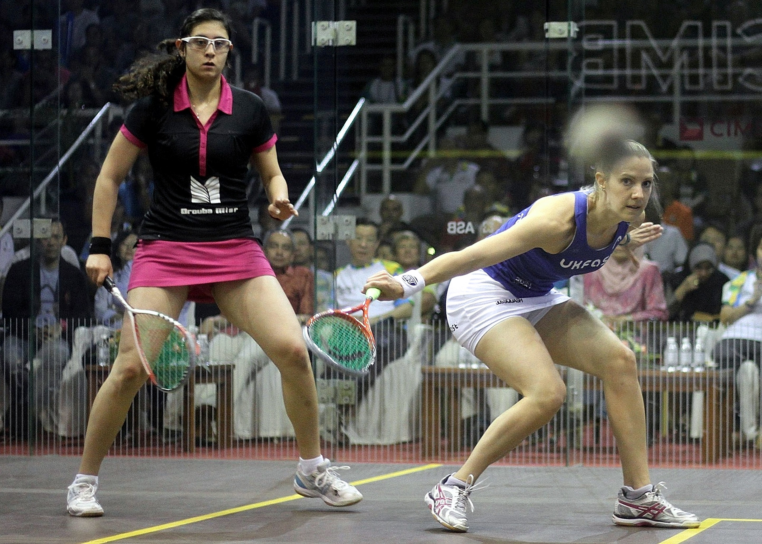 England's Laura Massaro (R) returns a shot against Nour El Sherbini of Egypt (L) during the CIMB Women's World Championship squash final against Nour El Sherbini of Egypt at the Spice Arena in Georgetown on March 23, 2014. Massaro won 11-7, 6-11, 11-9, 5-11, 11-9.      (AFP PHOTO)