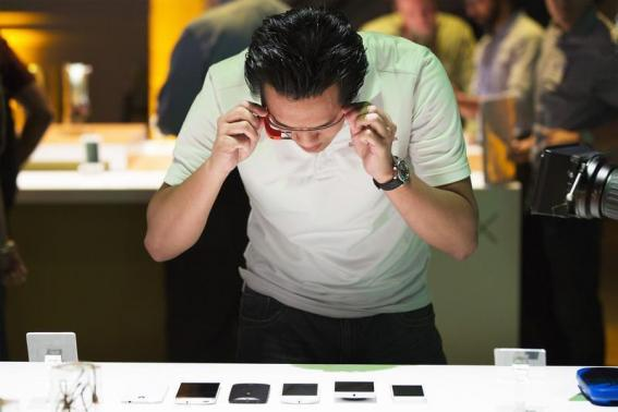 A man uses Google Glass to photograph examples of Motorola's new Moto X phone next to other mobile phones at a launch event in New York, on 1 August 2013. (REUTERS/Lucas Jackson)