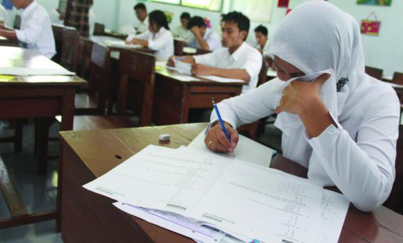 Use of new mobile phone apps such as Rivet, in addition to old techniques such as writing on rulers, walls, uploading documents onto calculators, or young girls placing such documents within their hijab, are some of the techniques that students have come to employ in order to help them engage in cheating on school exams (AFP Photo)