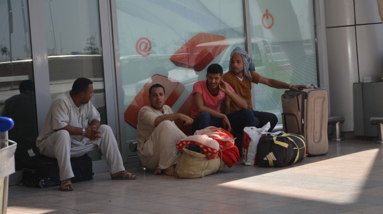 A group of Egyptian nationals sitting outside the Cairo International Airport shortly after their return from Libya in August (Photo Amany Kamal)