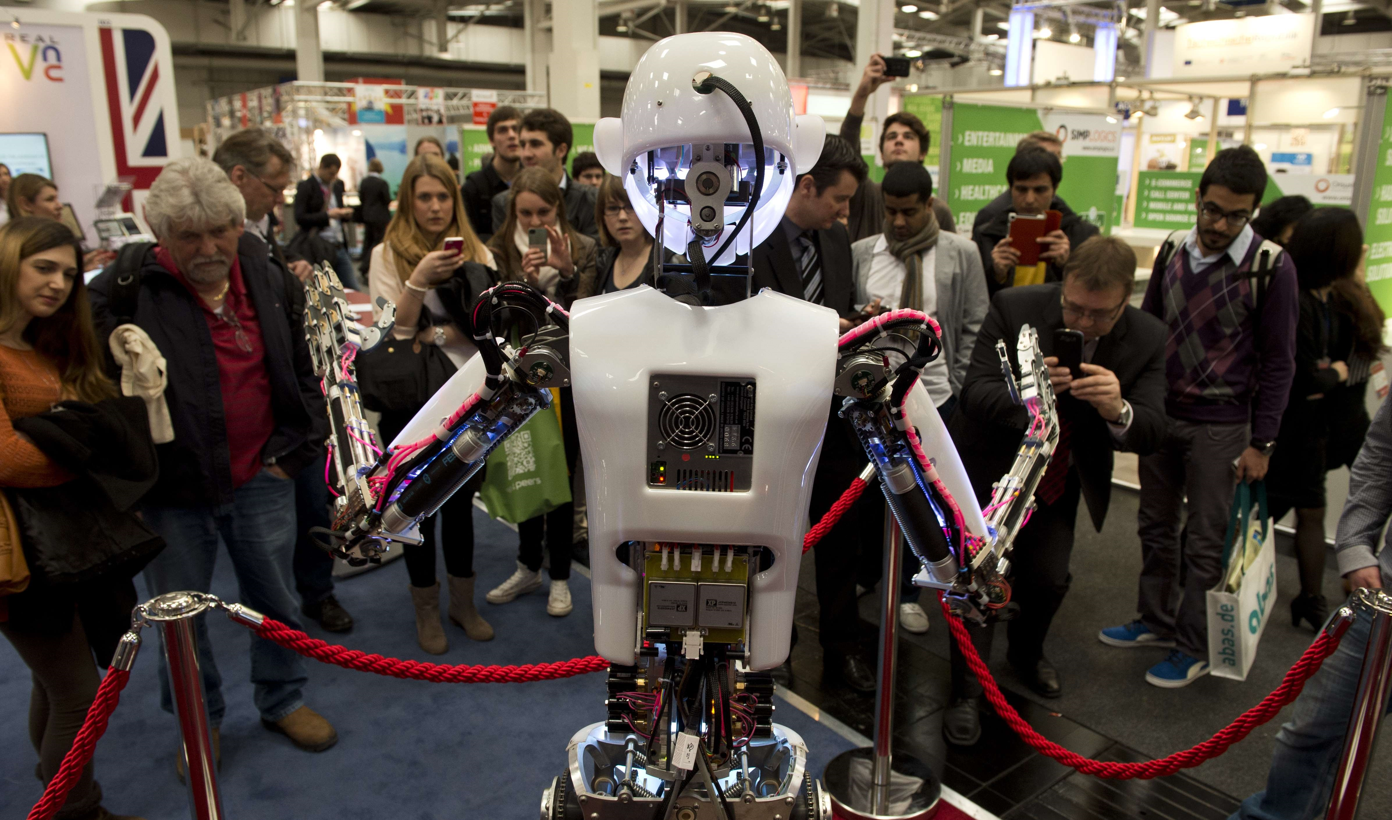 "The lifesize humanoid robot ""RoboThespian"" interacts with fair visitors at the Engineered Arts Ltd stand of the 2014 CeBIT computer technology trade fair on March 11, 2014 in Hanover, central Germany.  (AFP Photo)"
