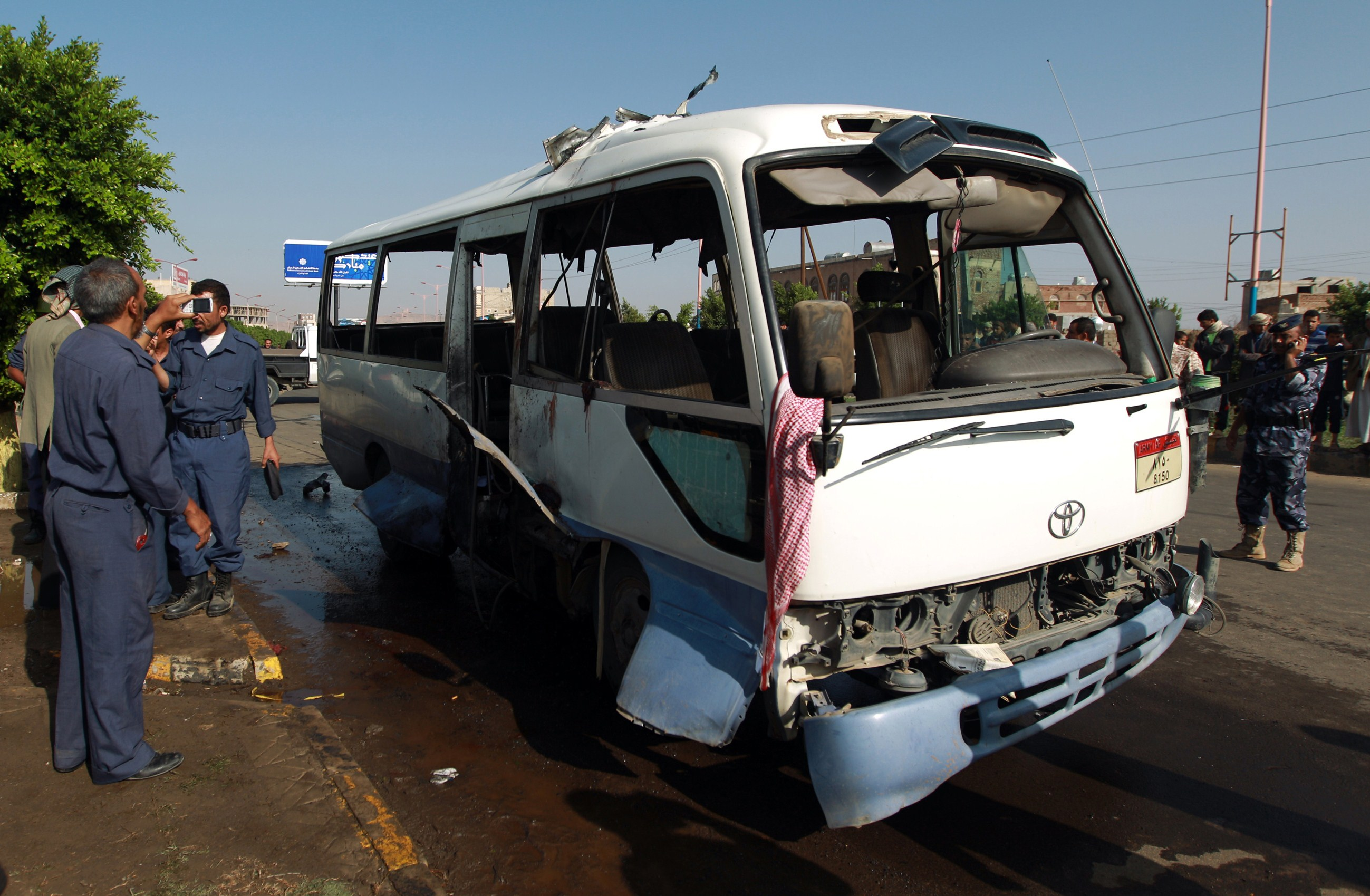 Yemeni security forces inspect a damaged military bus following a bomb blast in Sanaa on August 25, 2013. (AFP Photo)