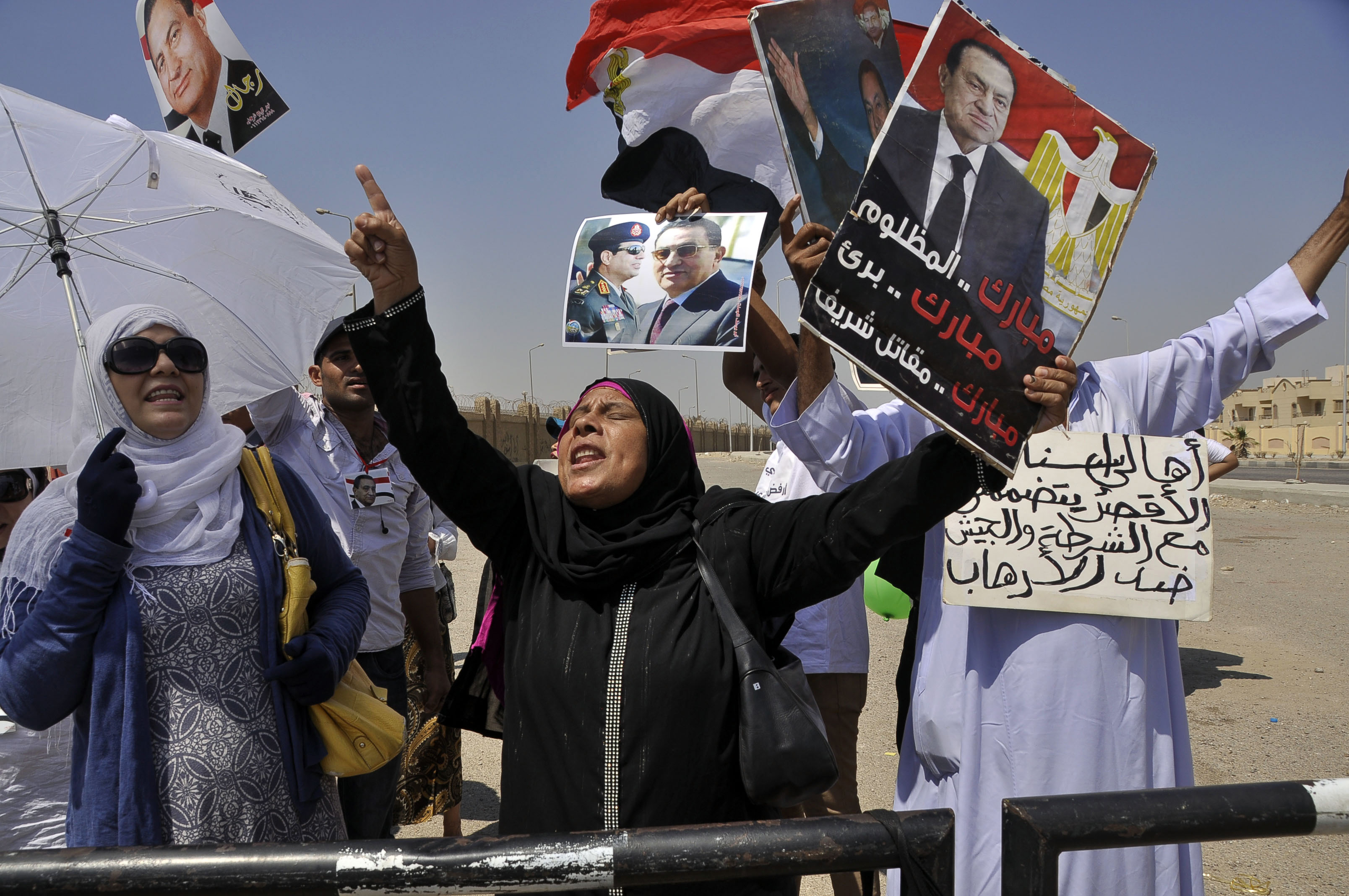Supporters of former Egyptian president Hosni Mubarak chant slogans and wave his portrait outside the Police Academy ahead of his trial on August, 25 2013 in Cairo.  (AFP Photo)