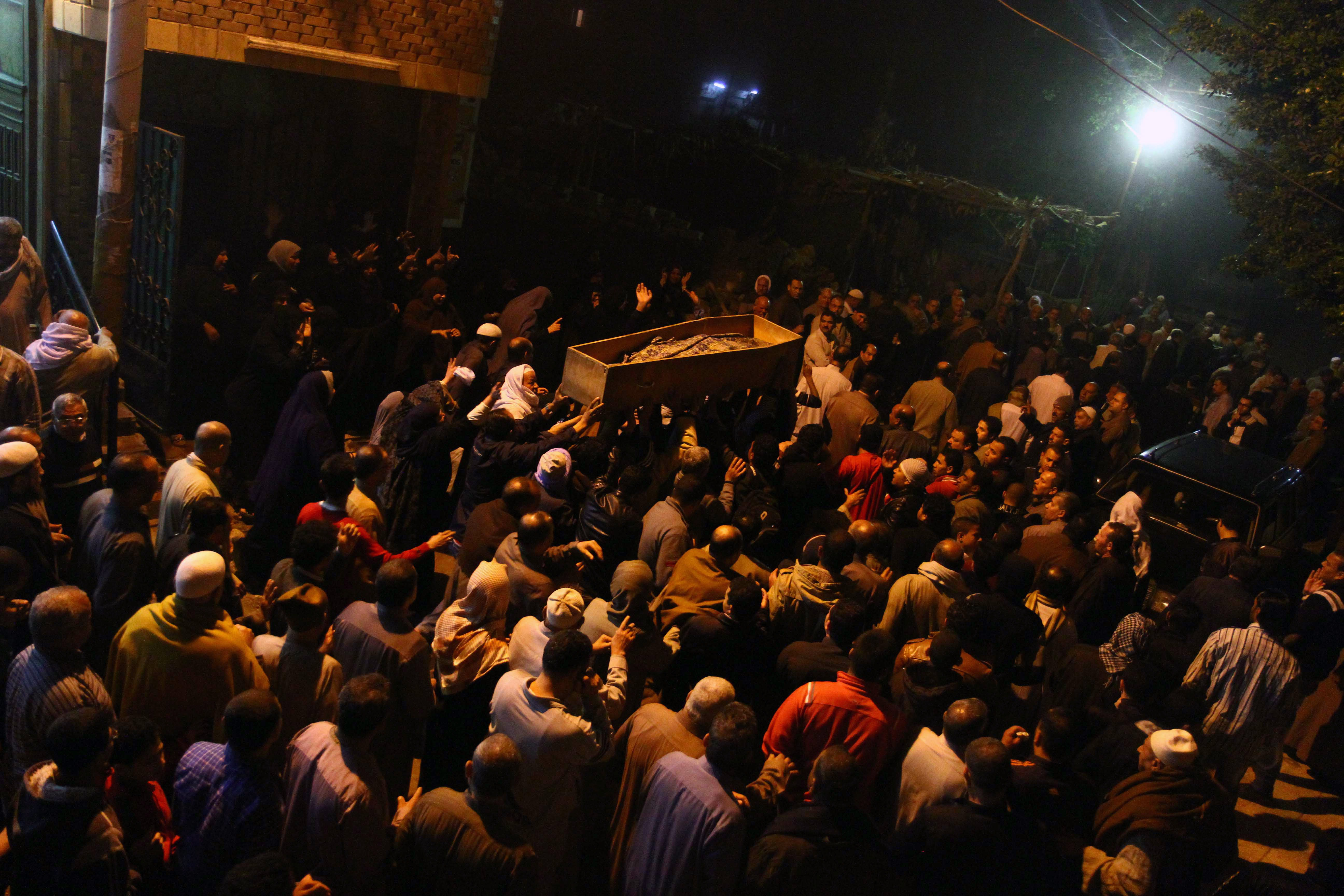 Mourners carry the coffin of Egyptian journalist Mayada Ashraf during her funeral in Estanhaa village at El-Monofia, 70 km north of Cairo, on March 29, 2014. Al-Dustour, a privately-owned newspaper, said on its website that its journalist Mayada was killed while covering clashes in the northern Cairo neighbourhood of Ein Shams.  (AFP PHOTO / AHMED MAHMOUD)
