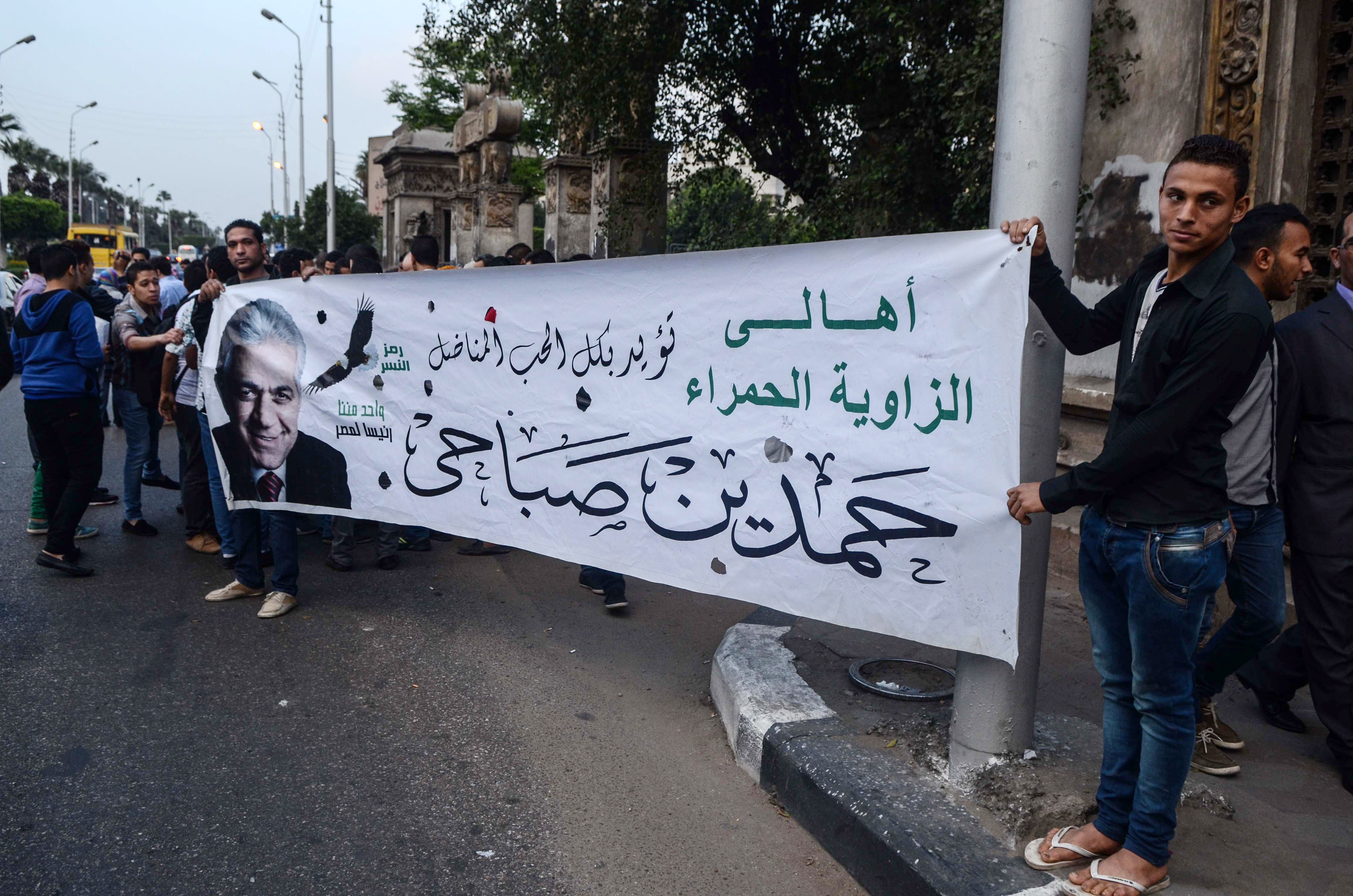 Supporters of Egyptian presidential hopeful Hamdeen Sabbahi hold a banner in his support on March 29, 2014 in the Egyptian capital Cairo. Egypt's army chief Abdel Fattah al-Sisi is assured of winning Egypt's forthcoming presidential vote but at the cost of reviving the era of strongman rule as he faces a dilapidated economy and rising militancy.   (AFP PHOTO / MOHAMED EL-SHAHED)