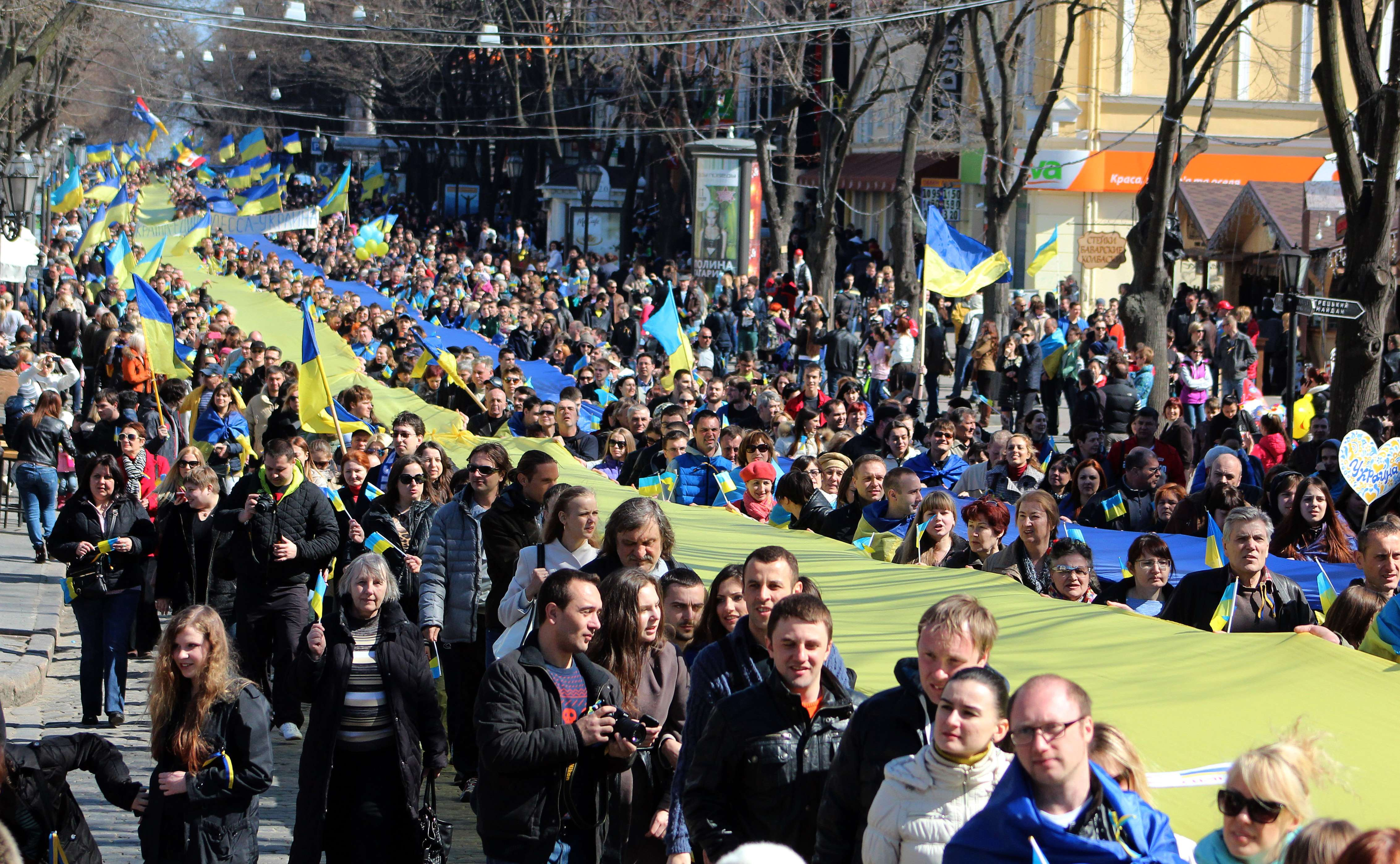 Pro-European Maidan supporters hold a large Ukrainian flag during a rally in Odessa on March 30, 2014. US Secretary of State John Kerry met his Russian counterpart today hoping to ease global tensions over the Kremlin's annexation of Crimea and sudden buildup of troops near Ukraine.  (AFP PHOTO / ALEXEY KRAVTSOV)