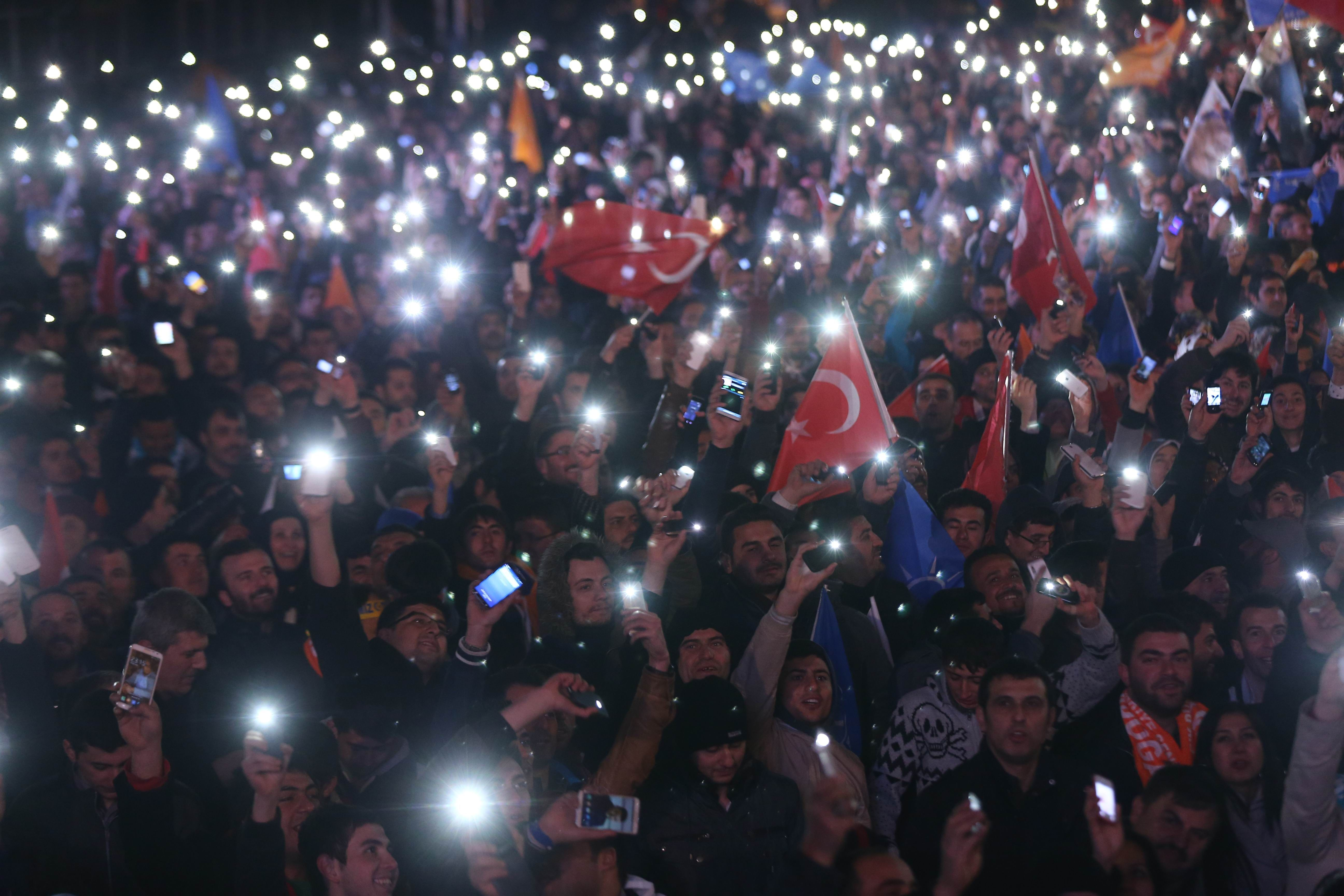 Supporters of Turkey's ruling AK party (AKP) cheer as they follow the election's results in front of the party's headquarters in Ankara, on March 30, 2014. The party of Turkish Premier Recep Tayyip Erdogan took a strong early lead in local elections, despite turbulent months marked by mass protests, corruption scandals and Internet blocks. A photo of Turkish Premier Recep Tayyip Erdogan is seen on the flag at right.      (AFP PHOTO / ADEM ALTAN)