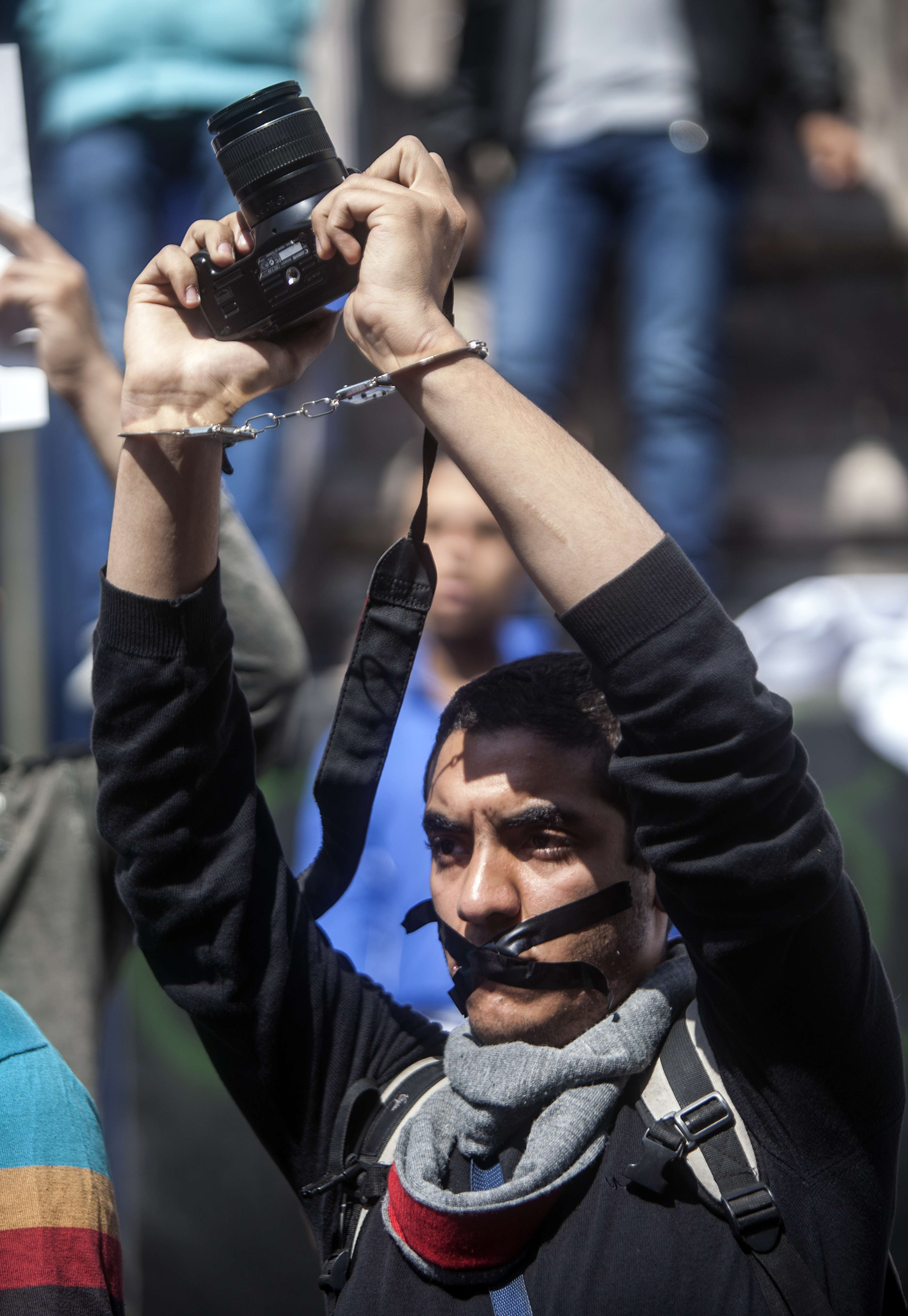 A photojournalists with his mouth tapped holds up his camera as he demonstrates with fellow colleagues in front of the journalist's syndicate in Cairo against repeated attacks on members of the press in Egypt on April 4, 2014.  (AFP PHOTO / MAHMOUD KHALED)