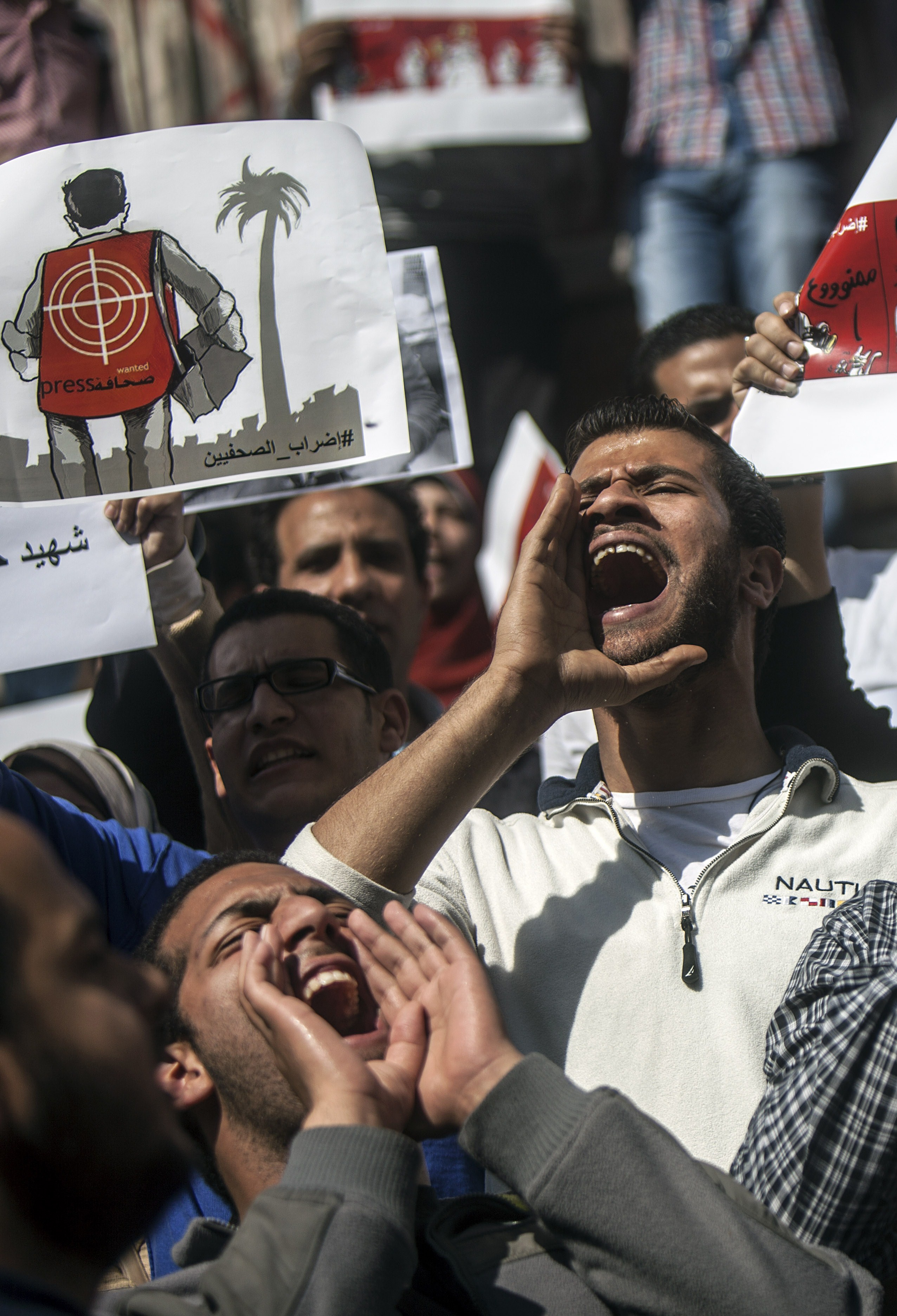 Journalists and photojournalists shout slogans as they demonstrate in front of the journalist's syndicate in Cairo against repeated attacks on members of the press in Egypt on April 4, 2014. (AFP FILE PHOTO / MAHMOUD KHALED)