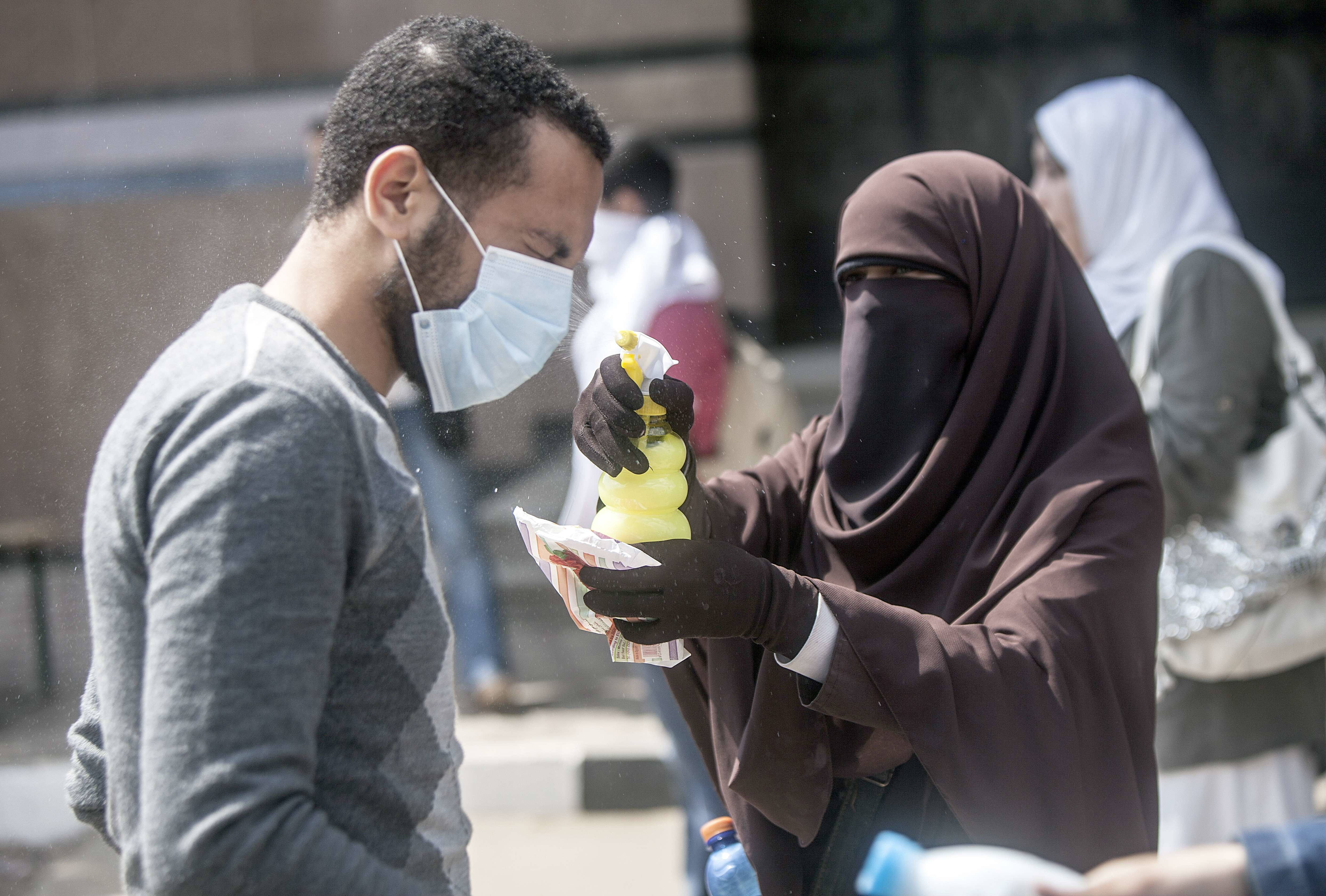 An Egyptian student has his eyes sprayed after being affected by tear gas fired by Egyptian riot police during clashes outside Cairo University, on April 9, 2014. (AFP Photo)