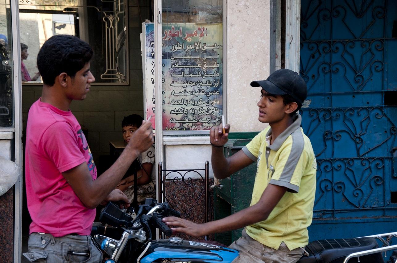 Teenagers smoke in Cairo's Al-Darb Al-Ahmar neighborhood  (Photo by Marwa Morgan)