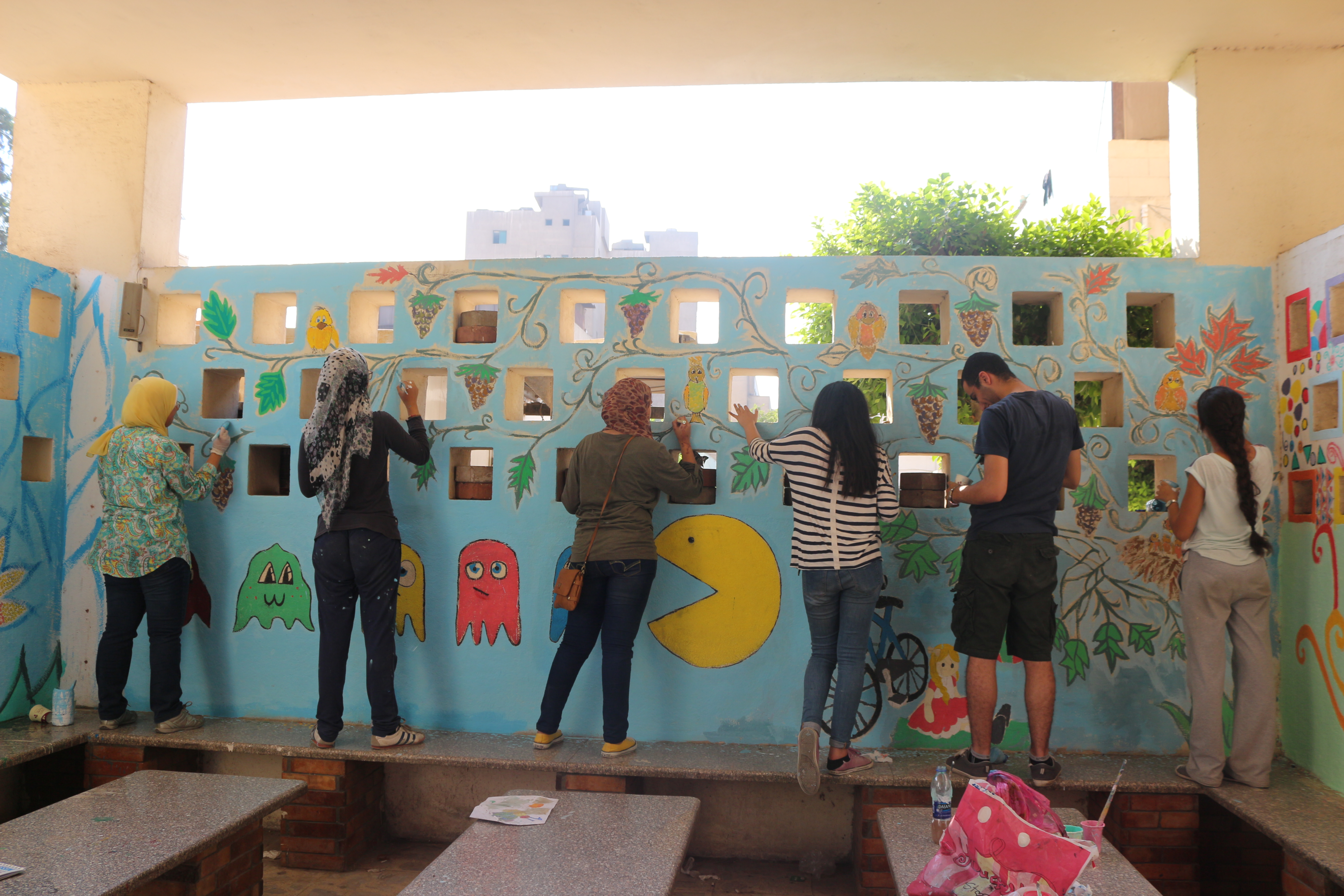 Volunteers add colours and drawings to the walls that the children see during their stay at the hospital (Leena ElDeeb)