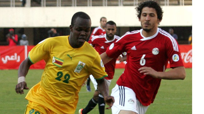 Zimbabwe's striker Knowledge Musona (L) vies with Egypt's Hegazi Ahmed (R) during a 2014 World Cup qualifying football match against Zimbabwe
