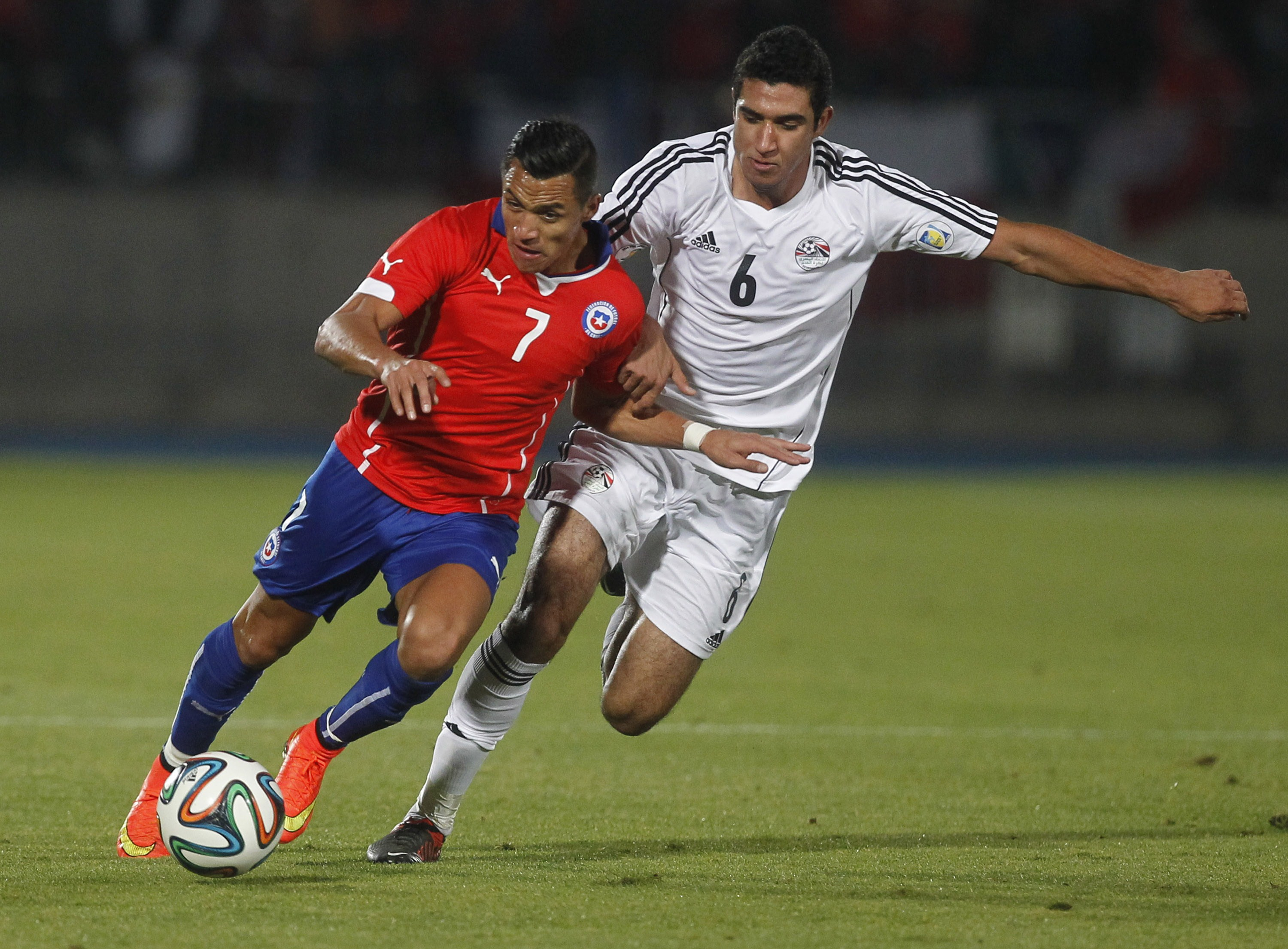 Chilean national team footballer Alexis Sanchez (L) vies for the ball with Egypt's Ramy Rabia (R) during a friendly match in Santiago, on May 30, 2014 less than a month before the start of the FIFA World Cup Brazil 2014.  (AFP PHOTO/CLAUDIO REYES)