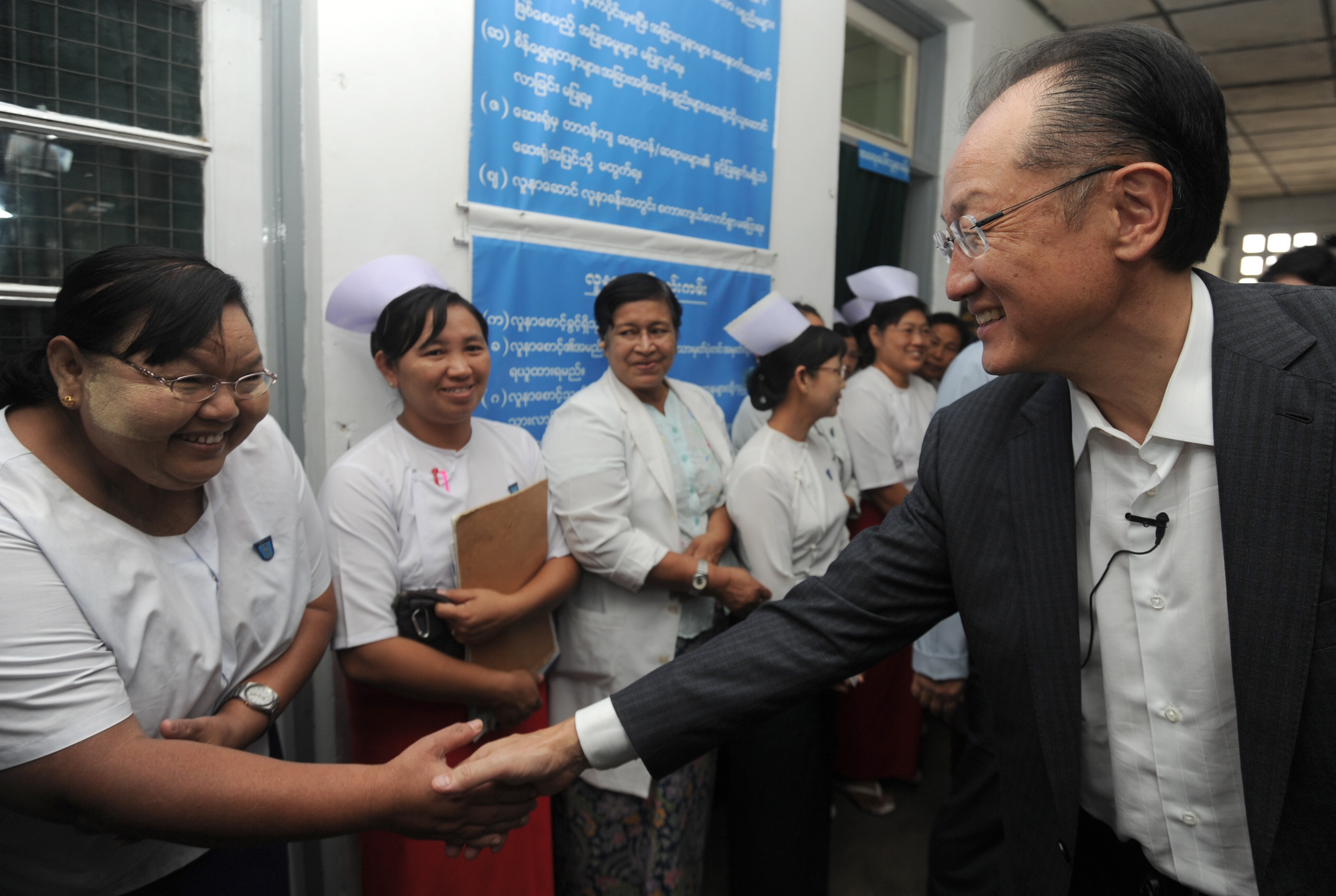 Jim Yong Kim, president of the World Bank Group, shake hands with a nurse as he arrives at a township hospital on the outskirts of Yangon on January 26, 2014 (AFP Photo)