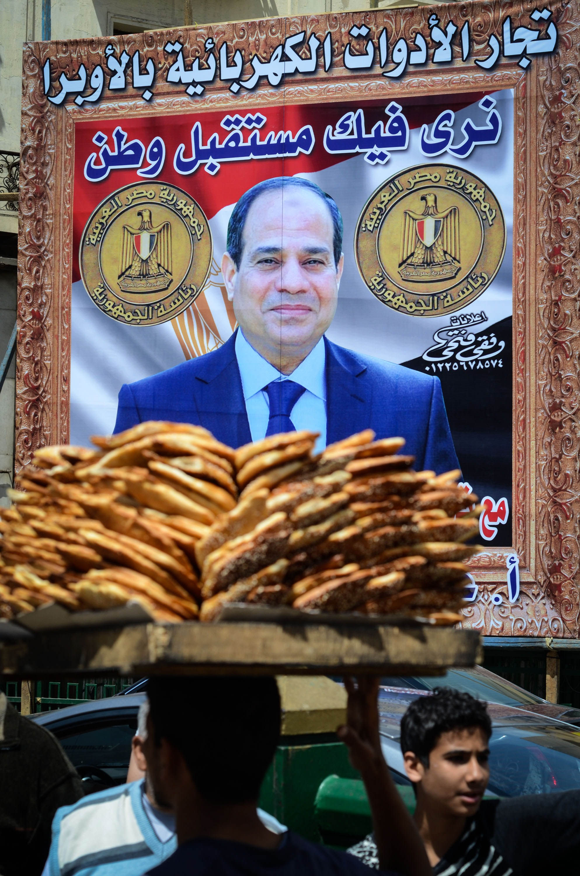 Egyptians walk past a poster bearing a portrait of retired army chief and presidential candidate Abdel Fattah al-Sisi on April 12, 2014 in the capital Cairo. Sisi is expected to win the May 26-27 presidential election riding on a wave of popularity for having removed the divisive Islamist president Mohamed Morsi after mass protests demanding his resignation. AFP PHOTO / MOHAMED EL-SHAHED