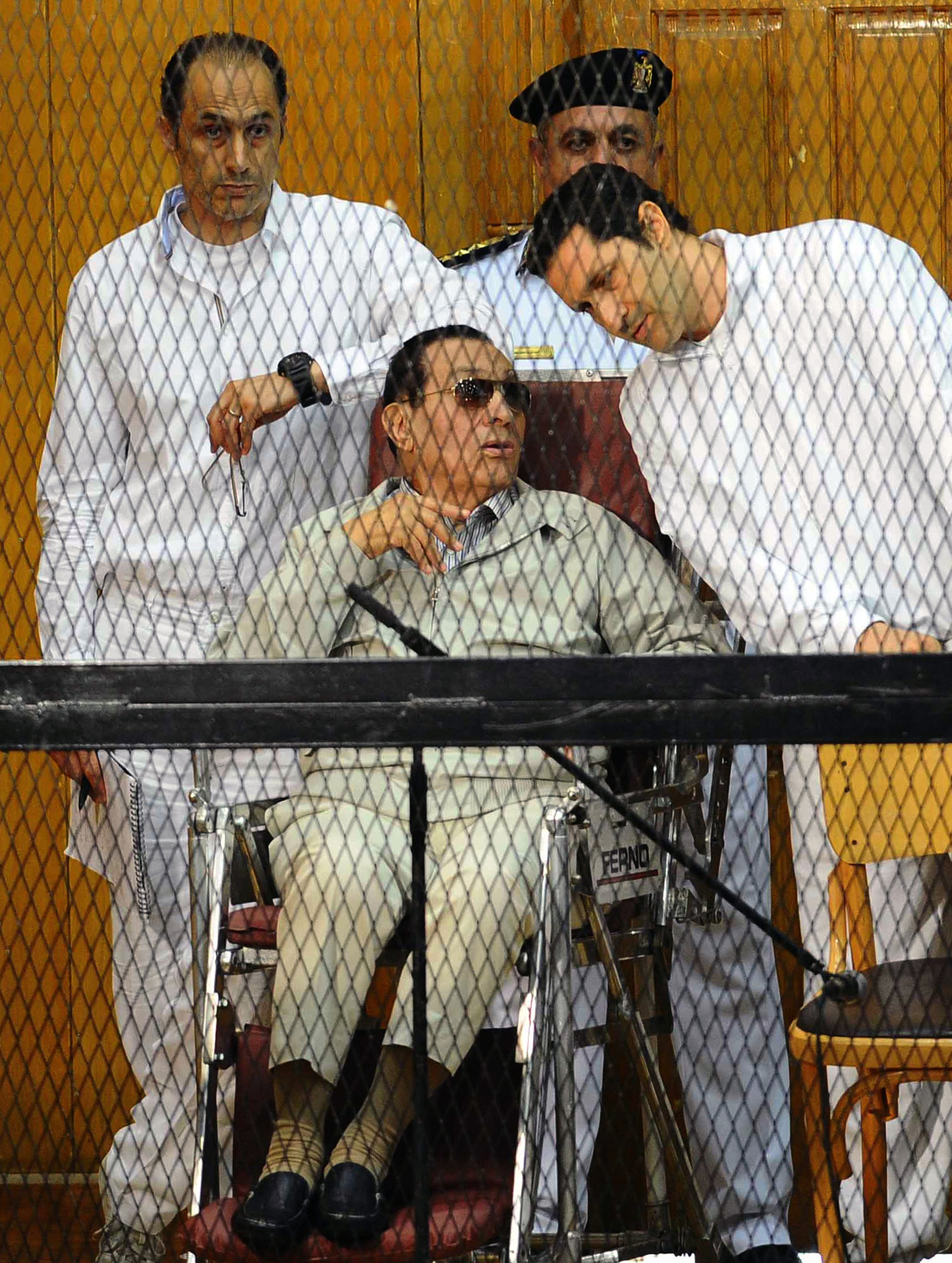 Egyptian toppled president Hosni Mubarak and his two sons Alaa (R) and Gamal stand behind bars during their trial at the Police Academy on September 14, 2013 in Cairo.  (AFP Photo)