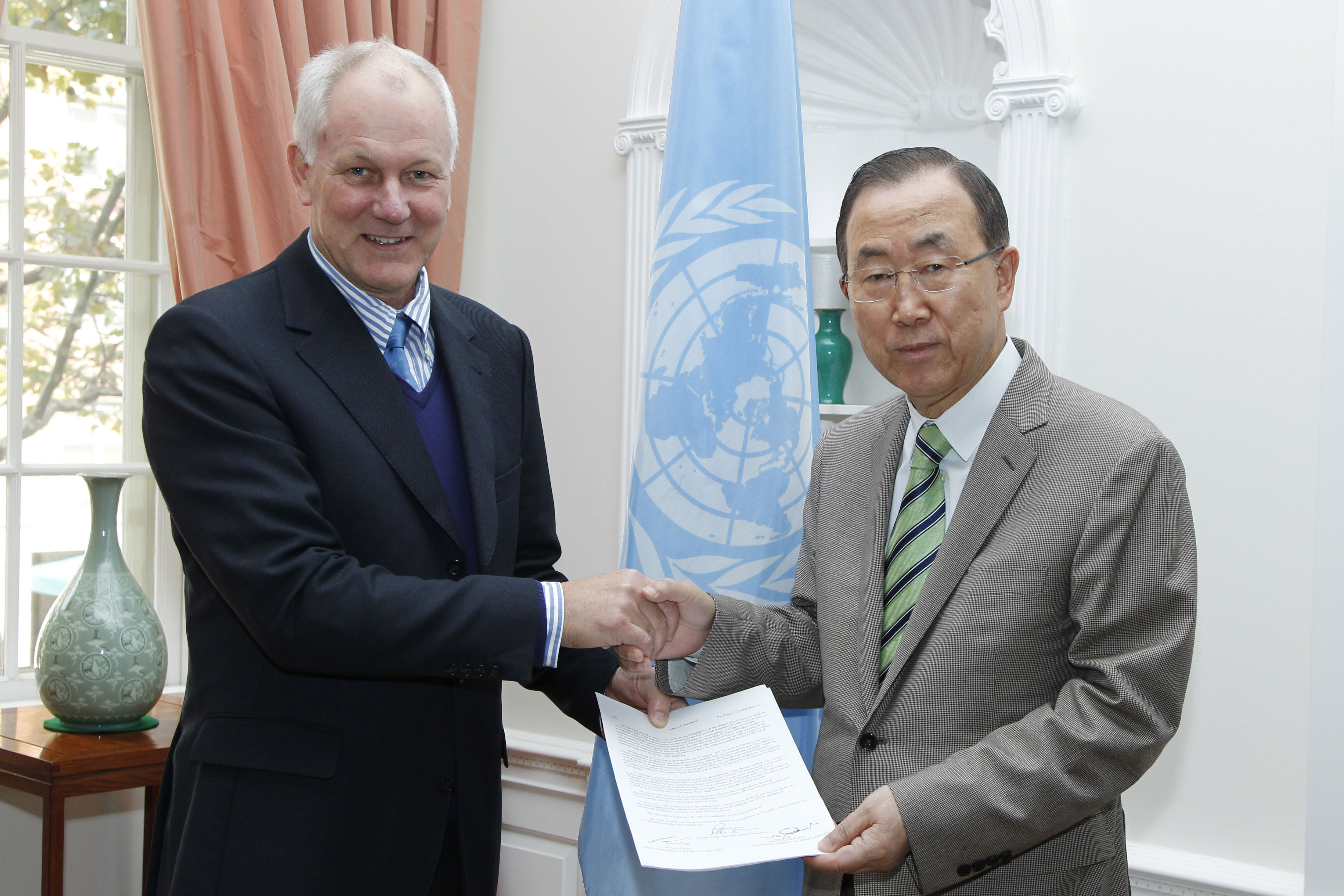 In this handout pool photo by UInited Nations shows Professor Ake Sellstrom (L), head of the chemical weapons team working in Syria, hands over the report on the 21 August 2013 Al-Ghouta massacre to Secretary-General Ban Ki-moon in New York on September 15, 2013. (AFP PHOTO / UN Photo / Paulo FILGUEIRAWS / POOL)