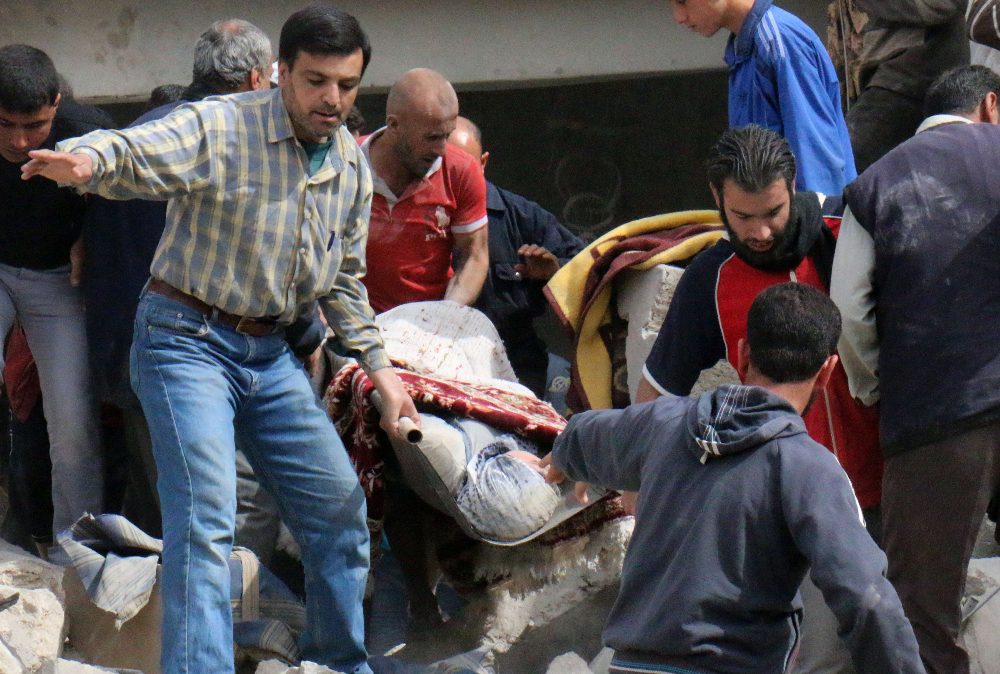 Syrian civilians carry a wounded woman following a reported barrel bomb attack by Syrian pro-government forces in Aleppo's Sakhur district on April 21, 2014. The Syrian Observatory for Human Rights, a Britain-based monitoring group relying on sources inside Syria, says more than 150,000 people have been killed since March 2011, and rebels hold vast swathes of territory. AFP PHOTO /ZEIN AL-RIFAI