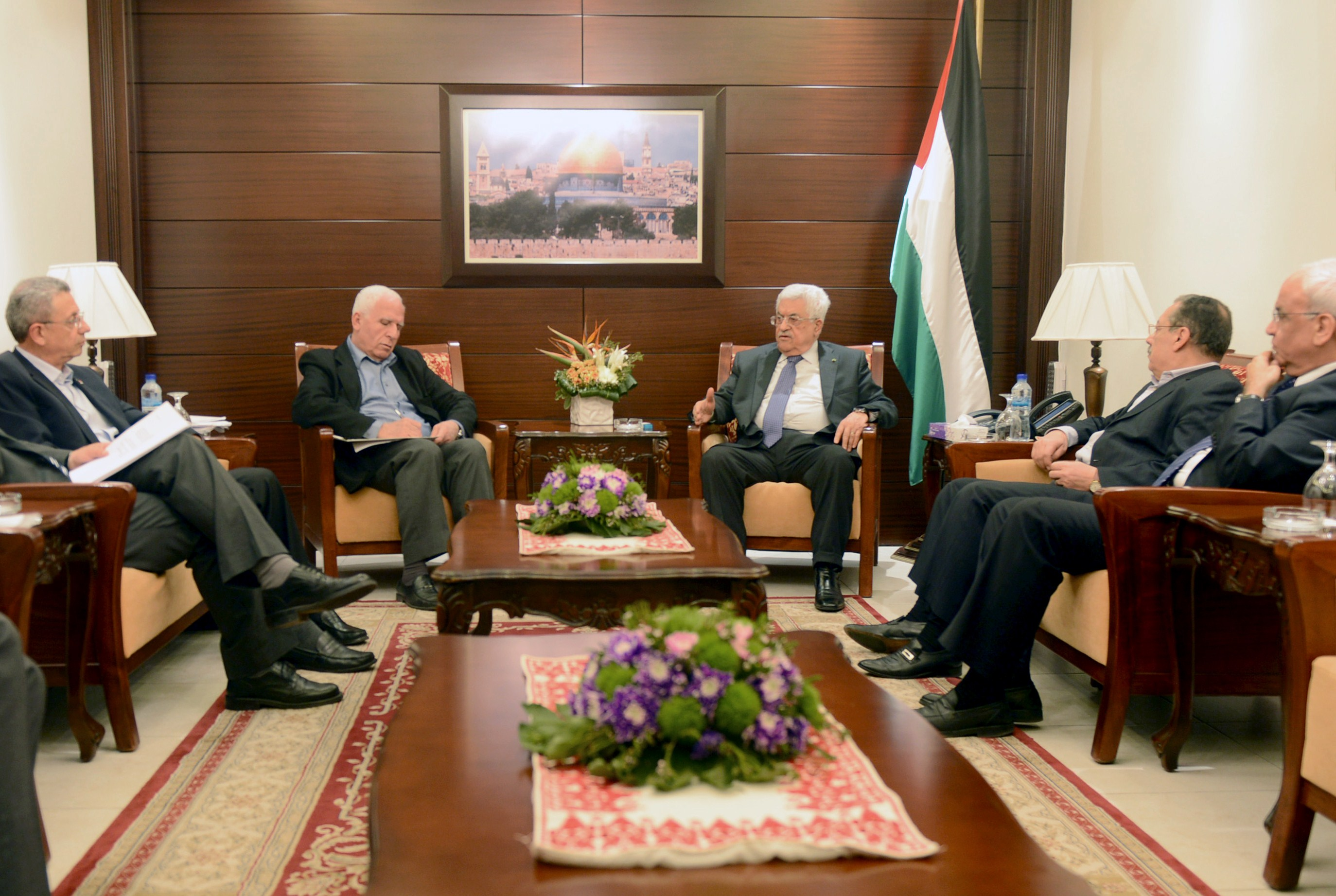 """A handout picture released by the Palestinian president's Press Office shows Palestinian president Mahmud Abbas (C-R) meeting with the delegation of the Palestine Liberation Organisation (PLO) in the West Bank city of Ramallah on April 22, 2014, ahead of its departure to Gaza for talks with Hamas. A senior Cairo-based Hamas official crossed yesterday from Egypt into the Gaza Strip ahead of a new attempt to reconcile the militant Islamist movement and its Palestine Liberation Organisation rivals. AFP PHOTO / PPO / THAER GHANAIM === RESTRICTED TO EDITORIAL USE / MANDATORY CREDIT """"AFP PHOTO / PPO / THAER GHANAIM"""" NO MARKETING / NO ADVERTISING CAMPAIGNS / DISTRIBUTED AS A SERVICE TO CLIENTS ==="""