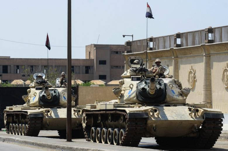 Egyptian military tanks are positioned outside the police institute near Cairo's Turah prison during the trial of three detained journalists with the Qatar-based Al-Jazeera broadcaster on April 10, 2014.  ( AFP Photo / Mohammed al-Shahed)