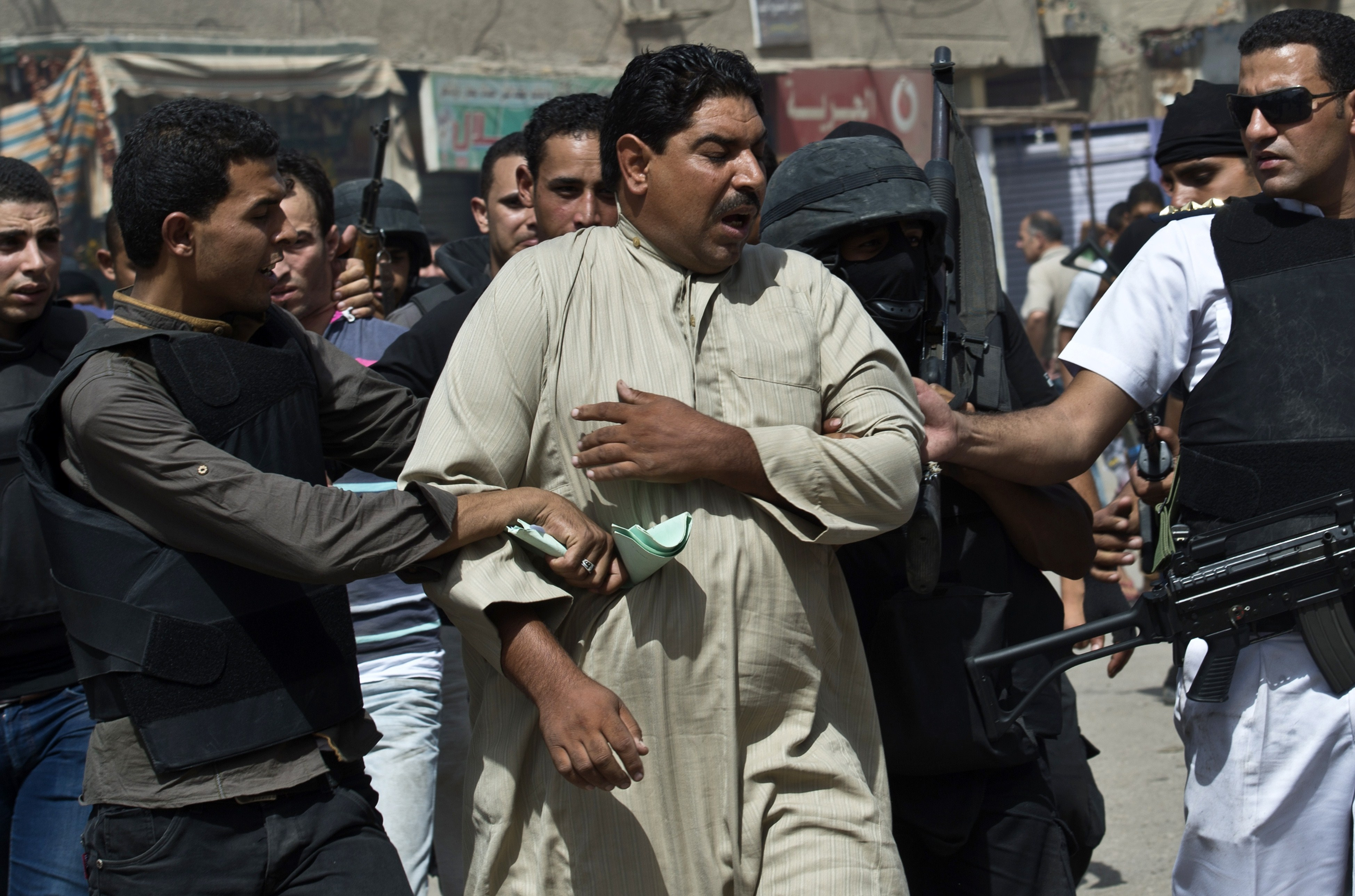 Egyptian armed policemen arrest a man during a raid in the village of Kerdassah on the outskirts of Cairo (AFP Photo)