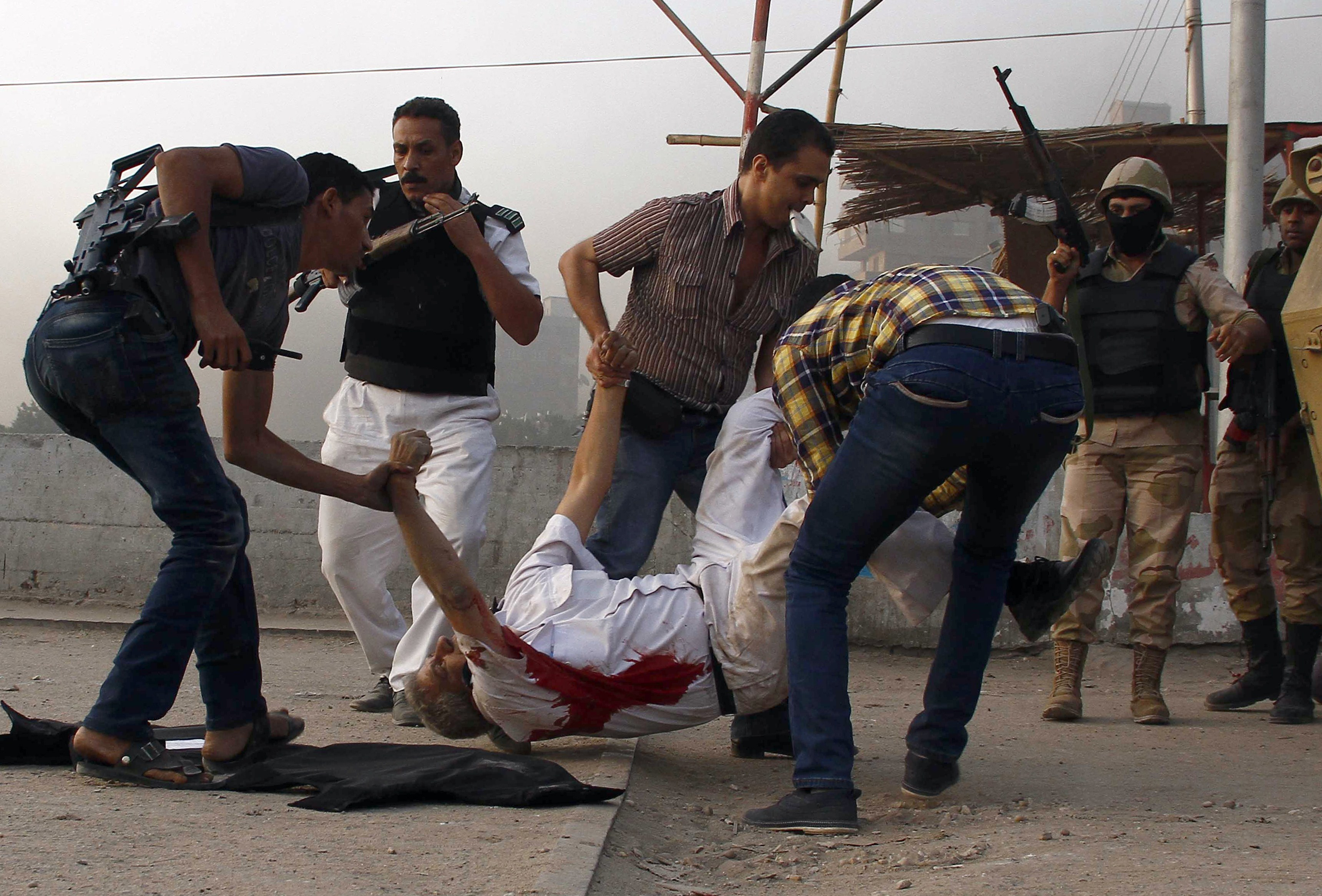 Egyptian policemen evacuate Giza security chief Nabil Farrag after he was shot during a raid in the village of Kerdassah on the outskirts of Cairo, on September 19, 2013. Farrag was killed when Egyptian security forces stormed Kerdassah in the latest crackdown on Islamist militants, security officials said.  (AFP PHOTO / AHMED ALI)