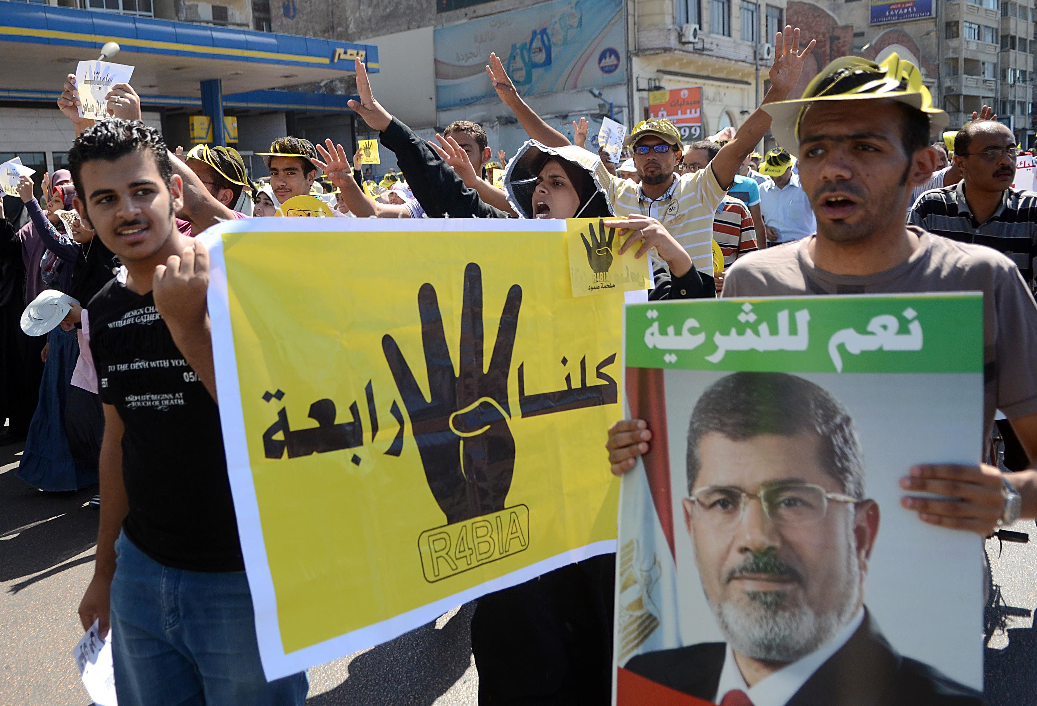 "Supporters of Egypt's ousted Islamist president Mohamed Morsi hold posters of the four finger symbol, known as ""Rabaa"", which means four in Arabic, to remember those killed in the crackdown on the Rabaa al-Adawiya protest camp in Cairo earlier in the year, as they take part in a demonstration against the military on September 20, 2013 along the seafront in the northern coastal city of Alexandria. Egypt's army-backed authorities arrested the spokesman of the Muslim Brotherhood on September 17 and froze the assets of other Islamists, in a new blow to deposed president Mohamed Morsi's supporters. (AFP PHOTO / STR)"