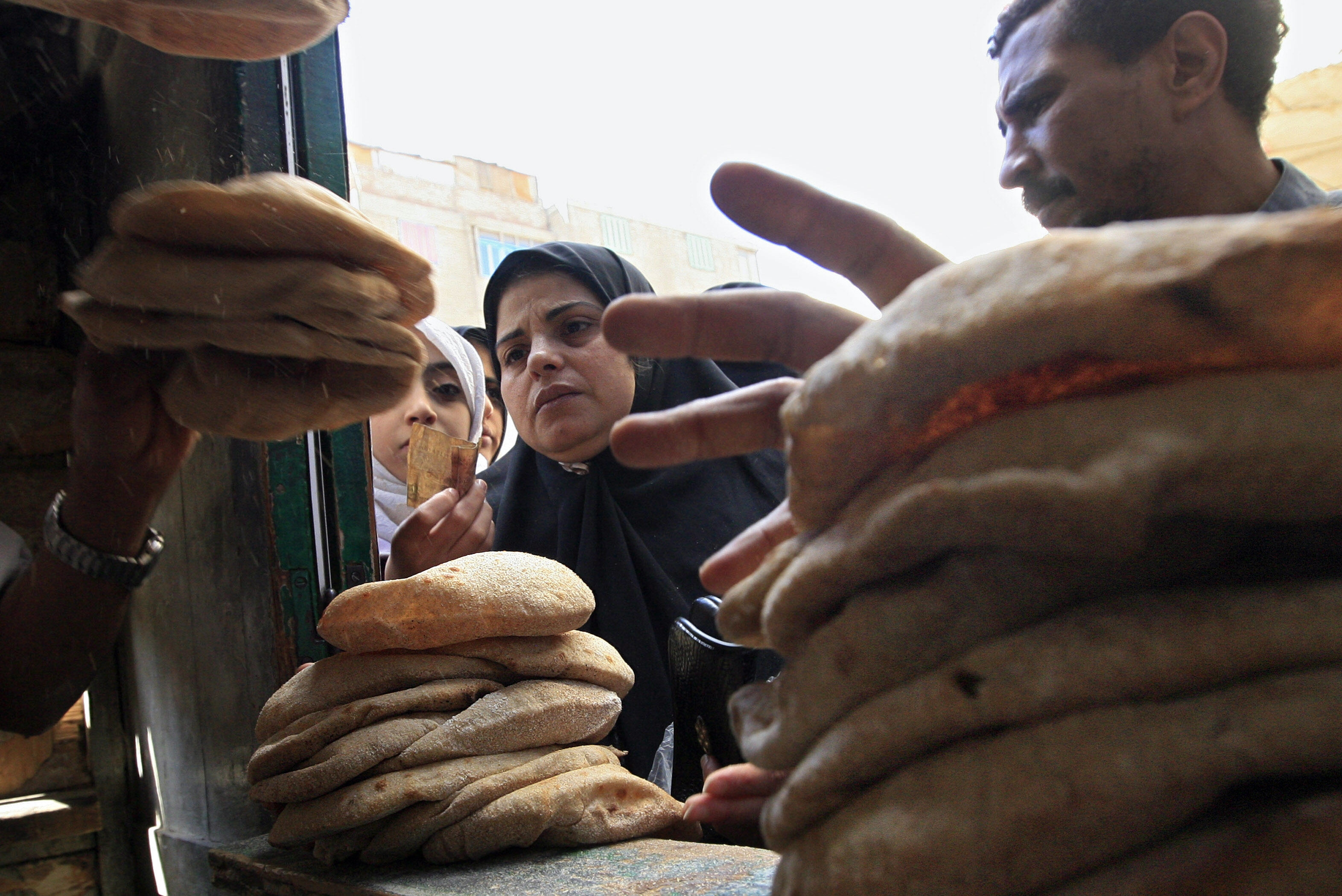 "A woman stands in line for subsidised bread. In a 2012 population survey, as many as 86% of Egyptians said their current income was ""insufficient for covering total monthly needs""  (AFP Photo)"