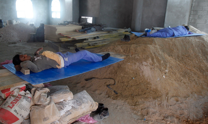 Migrant construction workers in Qatar resting during their lunch break  (Reuters Photo)
