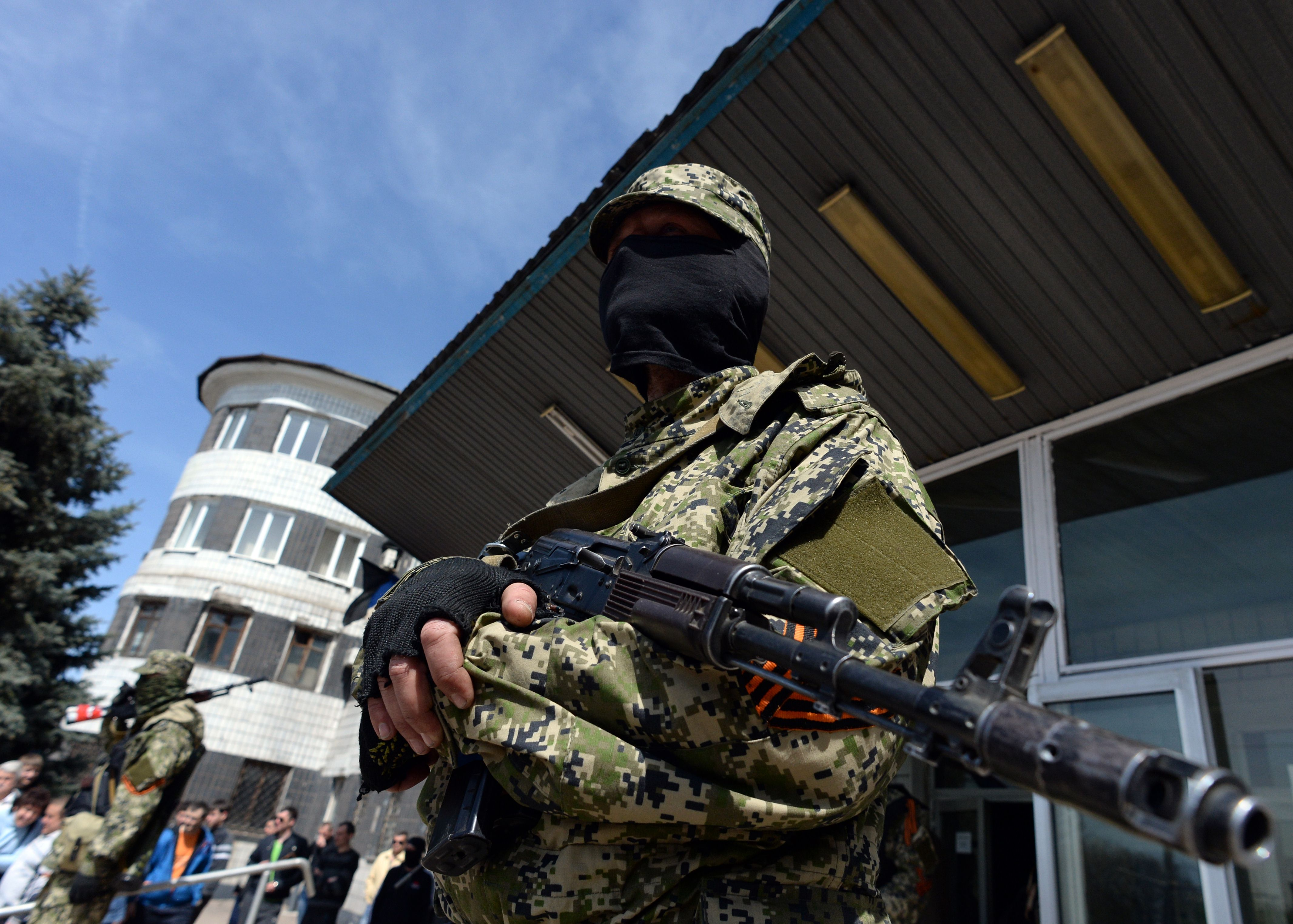 A pro-Russian armed man in military fatigues stands guard outside a regional administration building seized in the night by pro-Russian separatists, in the eastern Ukrainian city of Konstantinovka, on April 28, 2014. The United States moved to impose fresh sanctions against Russia today over the crisis in Ukraine, as pro-Kremlin gunmen seized another town in the east, further escalating tensions.  (AFP PHOTO / VASILY MAXIMOV)