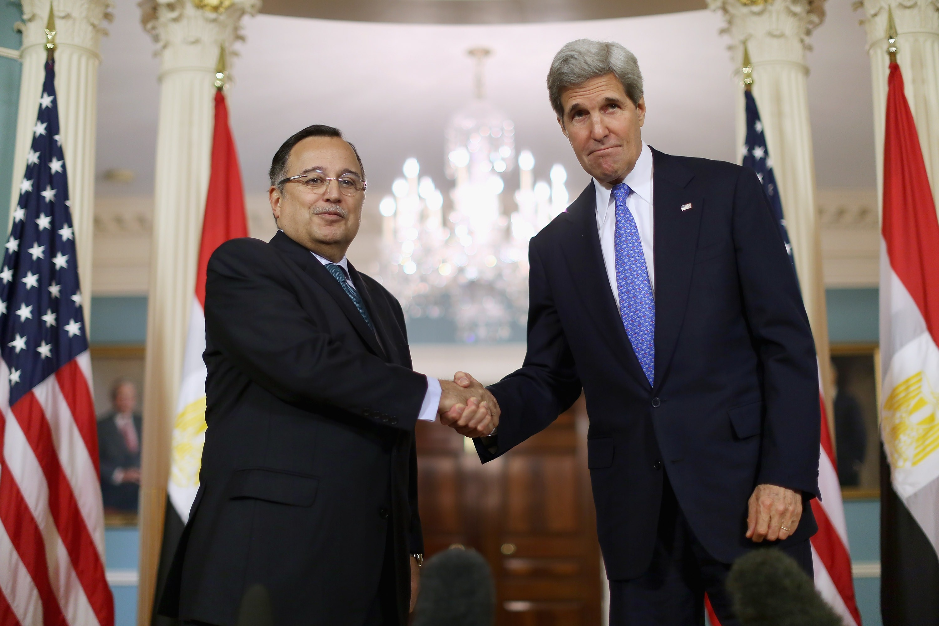 Secretary of State John Kerry (R) and Egyptian Foreign Minister Nabil Fahmy shake hands after making brief statements to the news media in the Treaty Room before meeting behind closed doors at the State Department April 29, 2014 in Washington, DC. Calling an Egyptian judge's sentencing of more than 680 people to death challenging, Kerry said the United States supports Egypt's attempts at democracy and its move to hold presidential elections in May. The mass trial and death sentences stemmed from last year's post-military coup violence and was denounced in the West and by human rights groups.    (Chip Somodevilla/Getty Images/AFP)