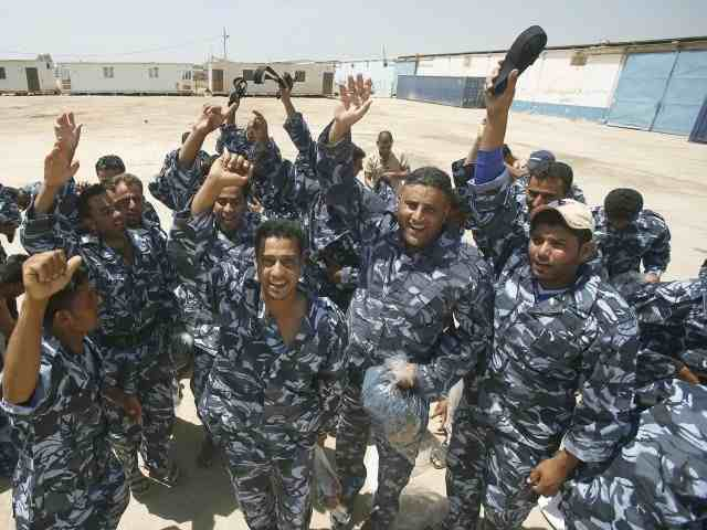 Iraqi volunteers wearing their new uniforms cheer as they gather at a center following an announcement by Iraqi Prime Minister Nuri al-Maliki that the Iraqi government would arm and equip civilians who volunteer to fight against militants.  (AFP Photo)