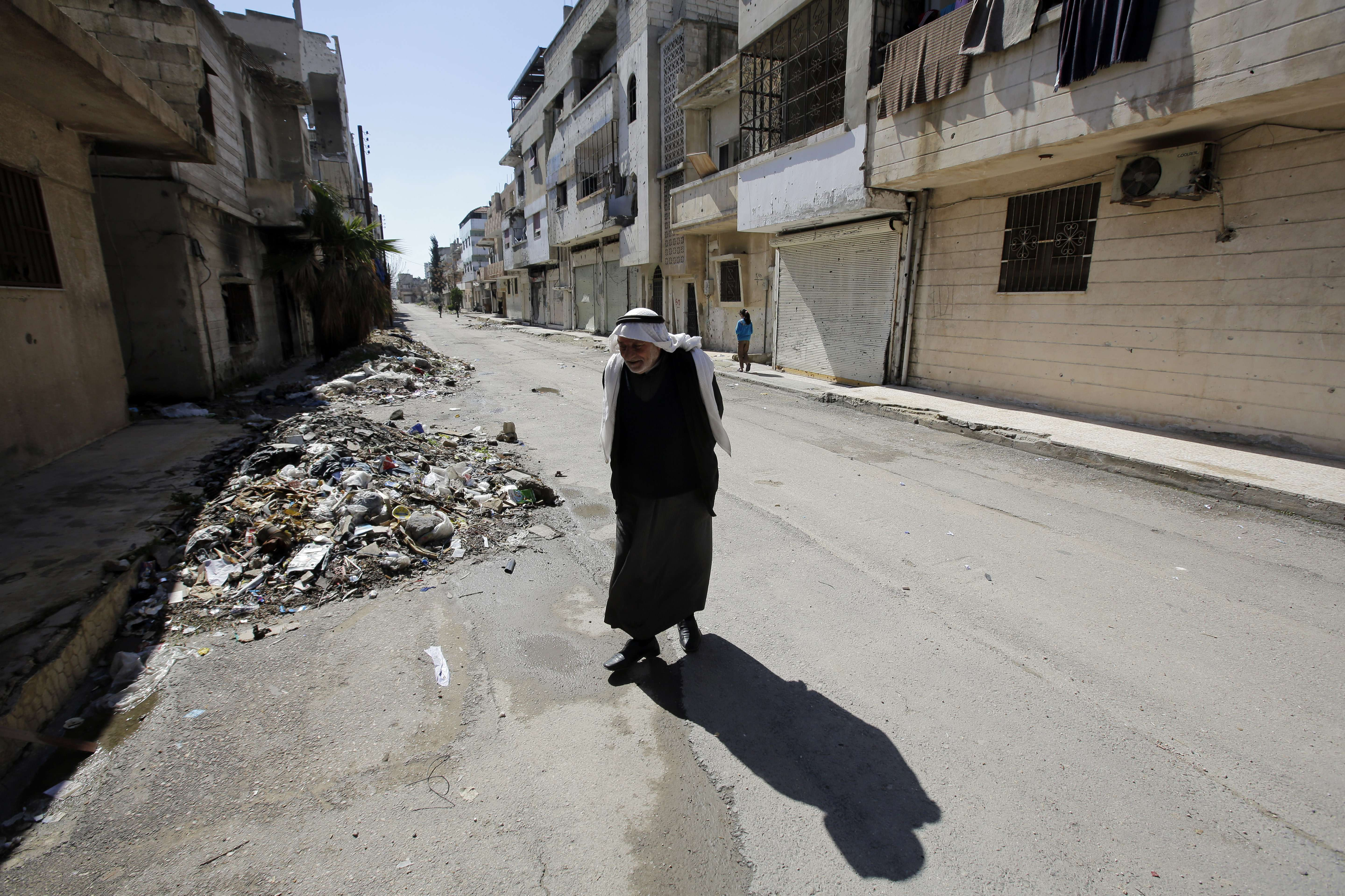 A file picture taken on March 15, 2014 shows a Syrian man walking in the once rebel-held neighbourhood of Baba Amro in the central Syrian city of Homs. Syria's government and rebels have reached a deal under which opposition fighters holed up in besieged parts of Homs city will withdraw during a ceasefire, an NGO said on May 2.  (AFP PHOTO/JOSEPH EID)