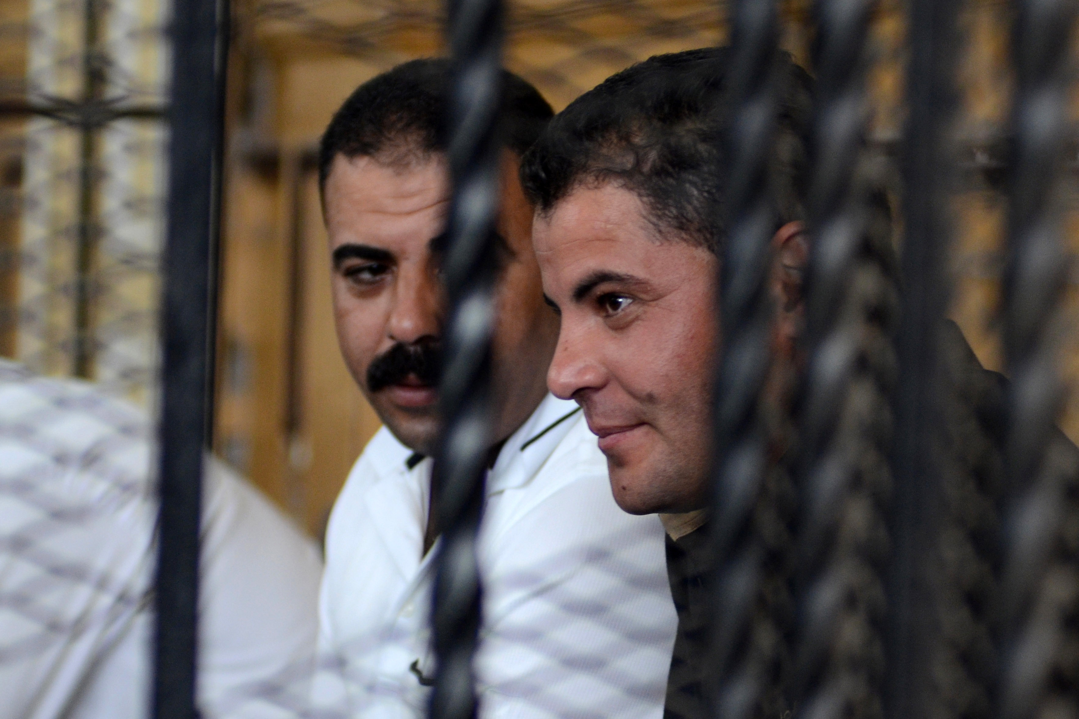 Egyptian police officers Awad Ismail Suleiman (L) and Mahmud Salah Amin, accused of using excessive force and killing 28-year-old blogger Khaled Said, sit behind bars in the defendants dock during their trial in Alexandria on October 1, 2013.  (AFP Photo)