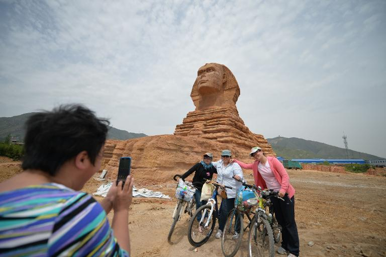 Residents pose for a photo before a full-size replica of the Great Sphinx of Giza in Donggou village in Shijiazhuang, north China's Hebei province on May 13, 2014. (AFP Photo)