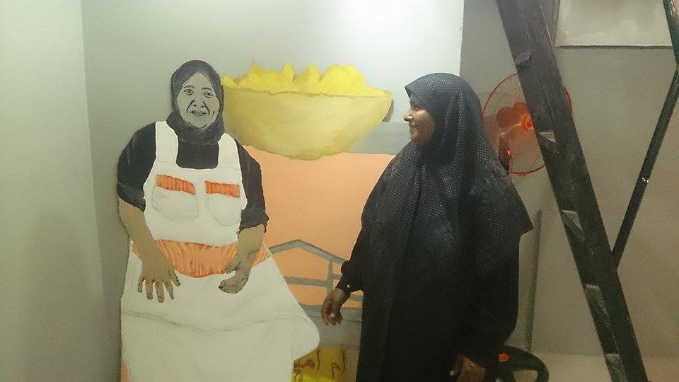 Om Amira, a popular potato seller in Bab El louq, poses with a spray paint portrait of herself. The portrait was displayed as part of the Kafahteya Street Vendors Project, the first exhibition at Heytan, a new gallery that celebrates street art in downtown, Cairo.  (Photo by Youssef Aziz)
