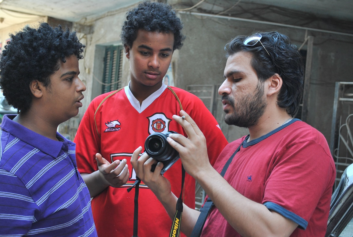 During workshops the young participants learn the tools of the trade, as shown here when they are told how to use a camera (Photo courtesy of Ahmed El-Hawary )