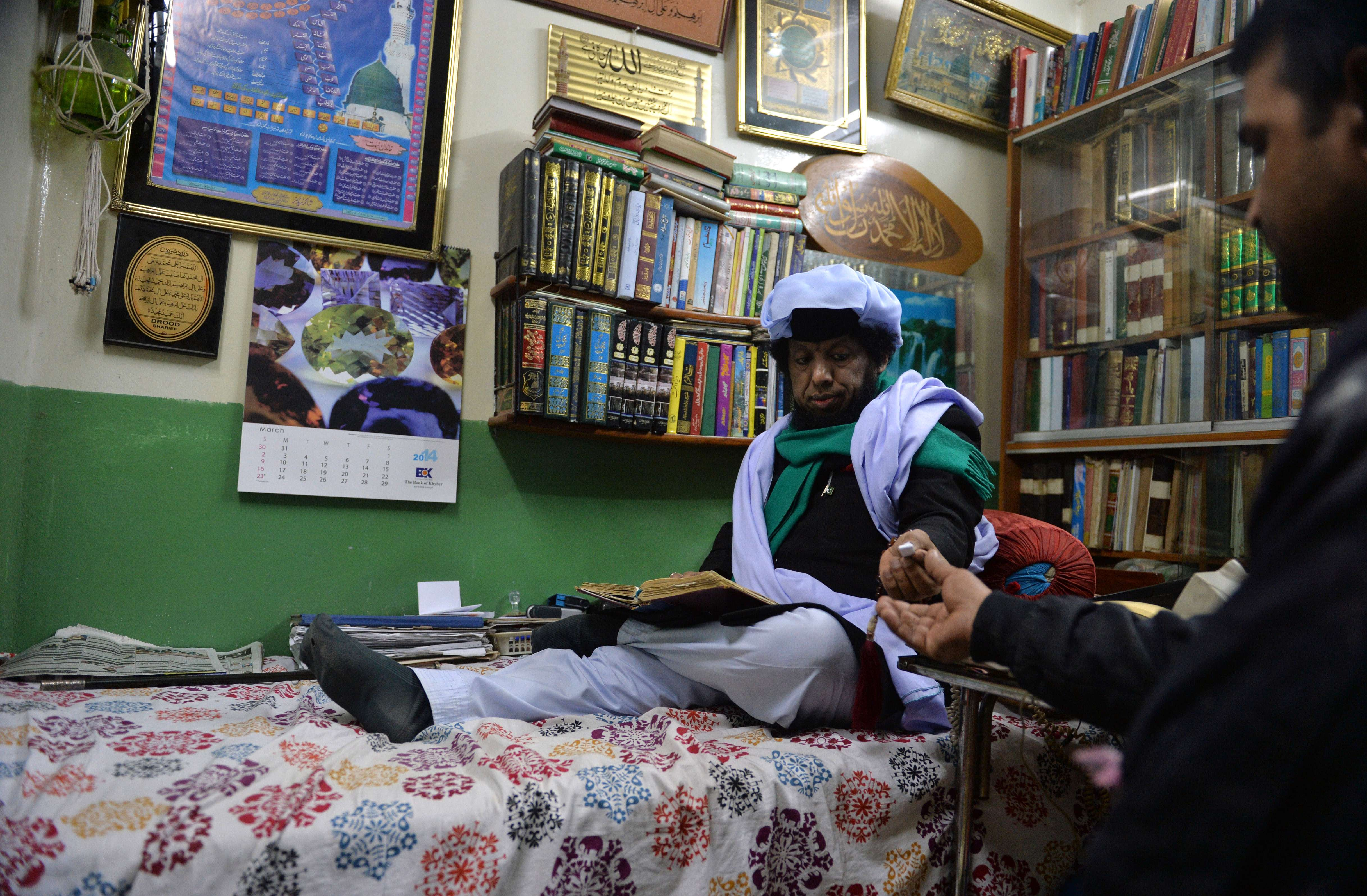 This photograph taken on March 2, 2014 shows a Pakistani Pir (Muslim saint) Syed Izhar Bokhari (L) giving a taweez or an amulet with written verses from the Koran to a devotee at his astaana (Sufi abode) in Rawalpindi, with a belief that it will resolve his problems. From winning the heart of your beloved to getting a promotion at work, Pakistan's black magicians say there is nothing they can't help you achieve – for a humble donation  (AFP Photo / Aamir Qureshi)