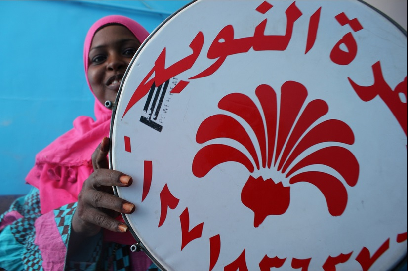 A woman upholds a drum with a Nubian logo (Photo by Aurora Ellis)