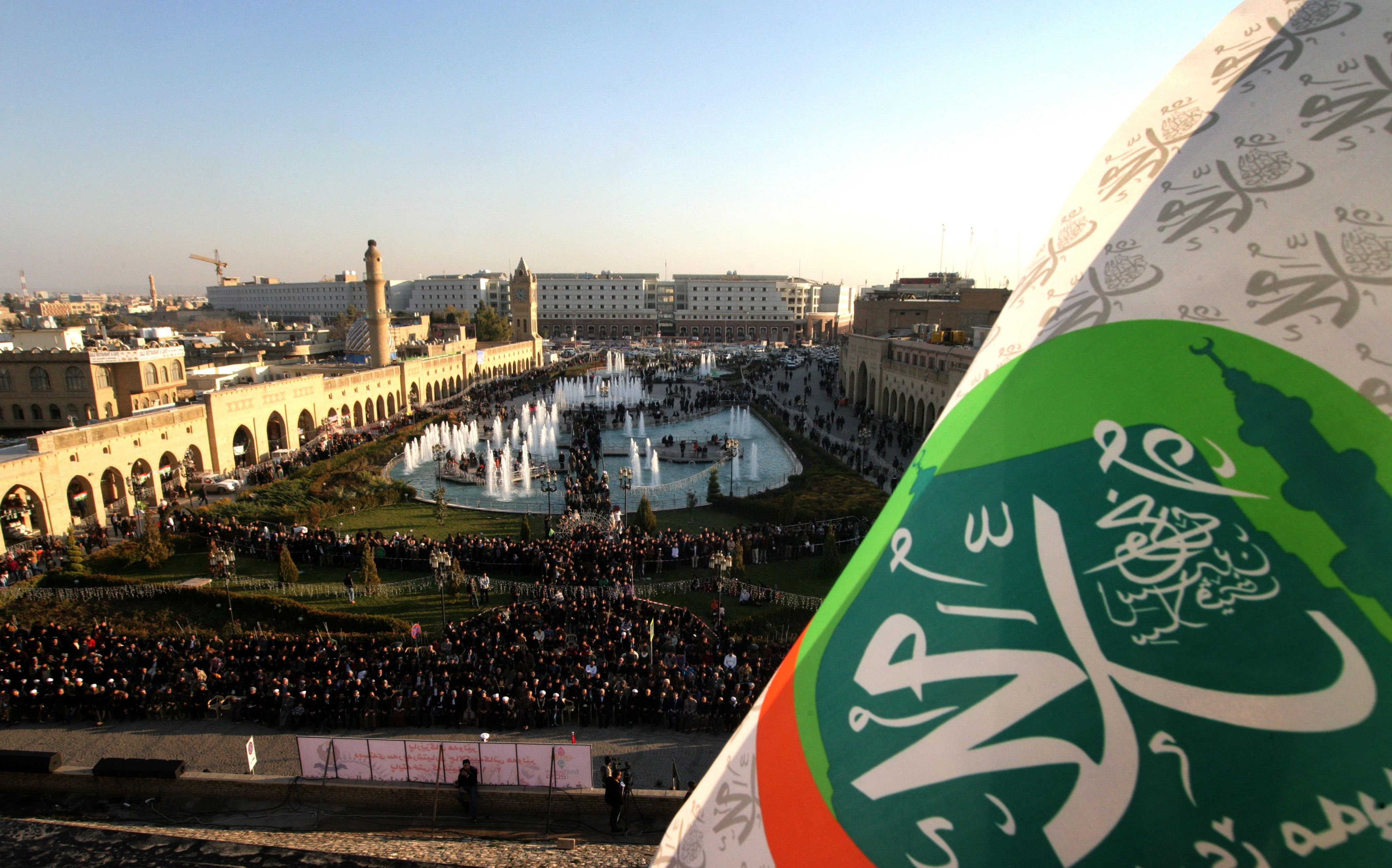 A flag bearing the name of Prophet Muhammad flies in the foreground as Iraqi Kurds gather in the centre of the capital of the autonomous Kurdish Arbil region of northern Iraq the evening before the celebrations  (AFP Photo / Safin Hamed)