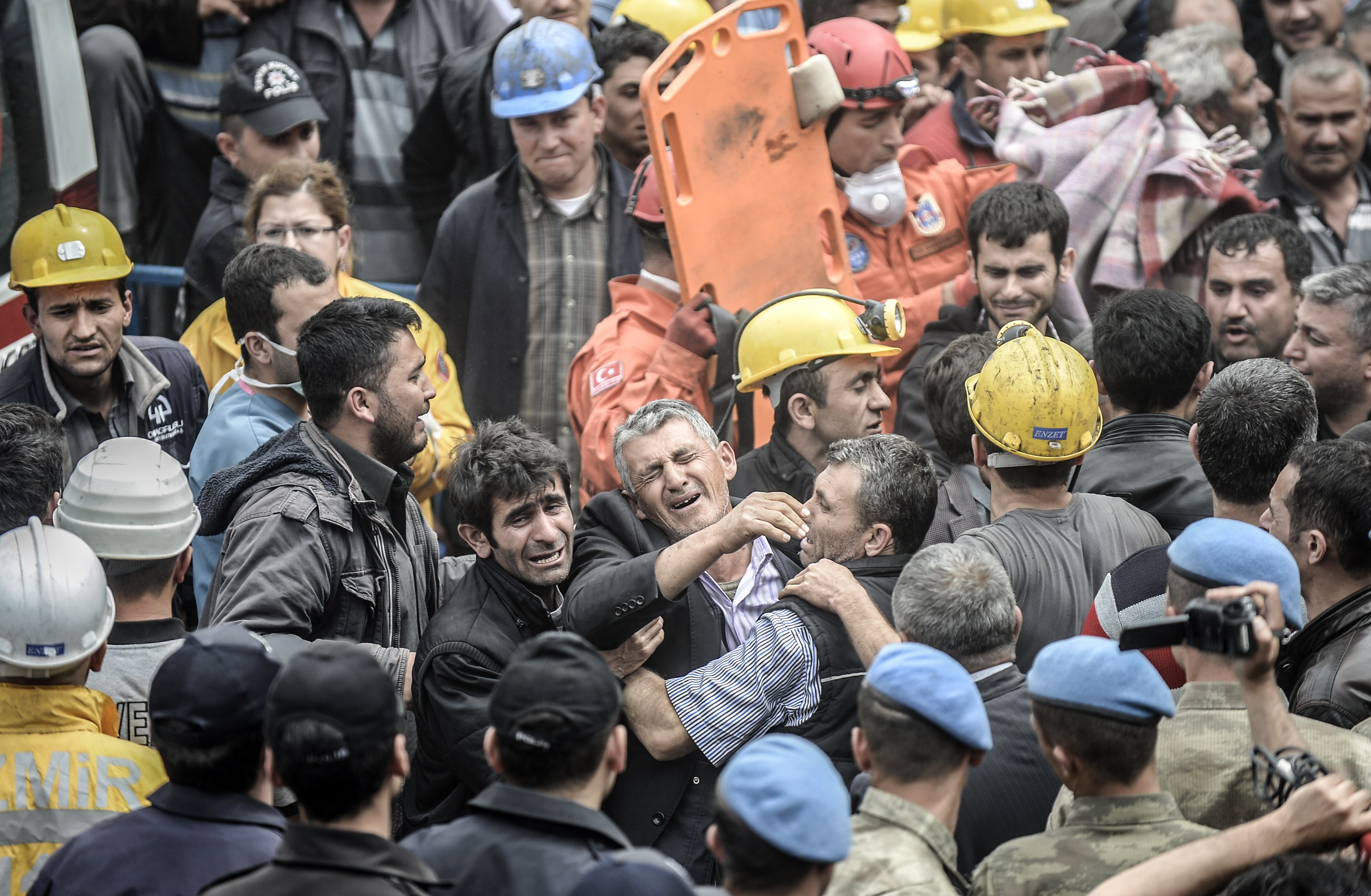 Miners react as bodies of their dead co-workers are carried out of the mine after searching for hours hundreds of their colleagues who remain trapped underground on May 14, 2014 after an explosion and fire in their coal mine in the western Turkish province of Manisa killed at least 201 people.    (AFP PHOTO/BULENT KILIC)