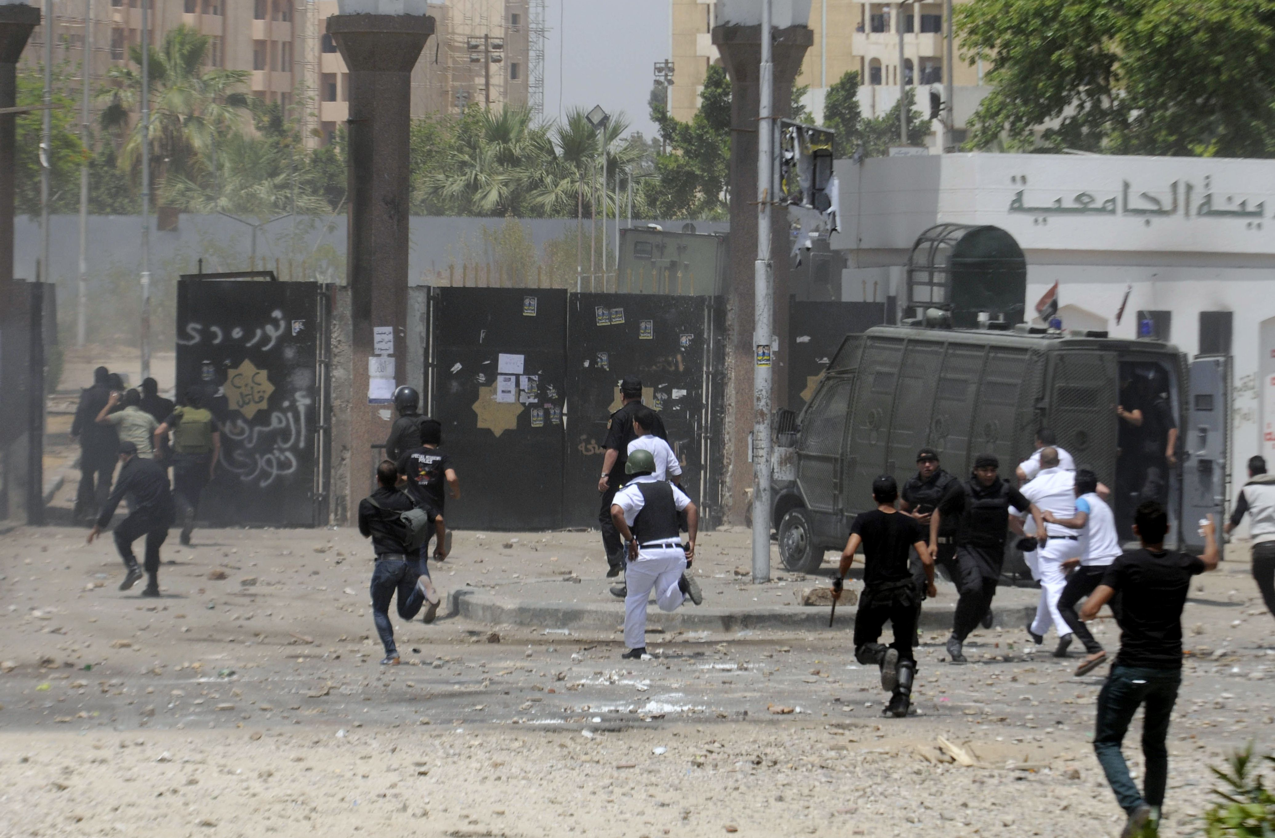 Egyptian policemen run towards the entrance of the al-Azhar university campus in Cairo on May 16, 2014 during clashes with students. Students supporters of deposed Islamist leader Mohammed Morsi regularly stage protests calling for his release at universities, in particular at Cairo's Al-Azhar university, a prestigious seat of Sunni Islamic learning. (AFP PHOTO / TAREK WAJEH)