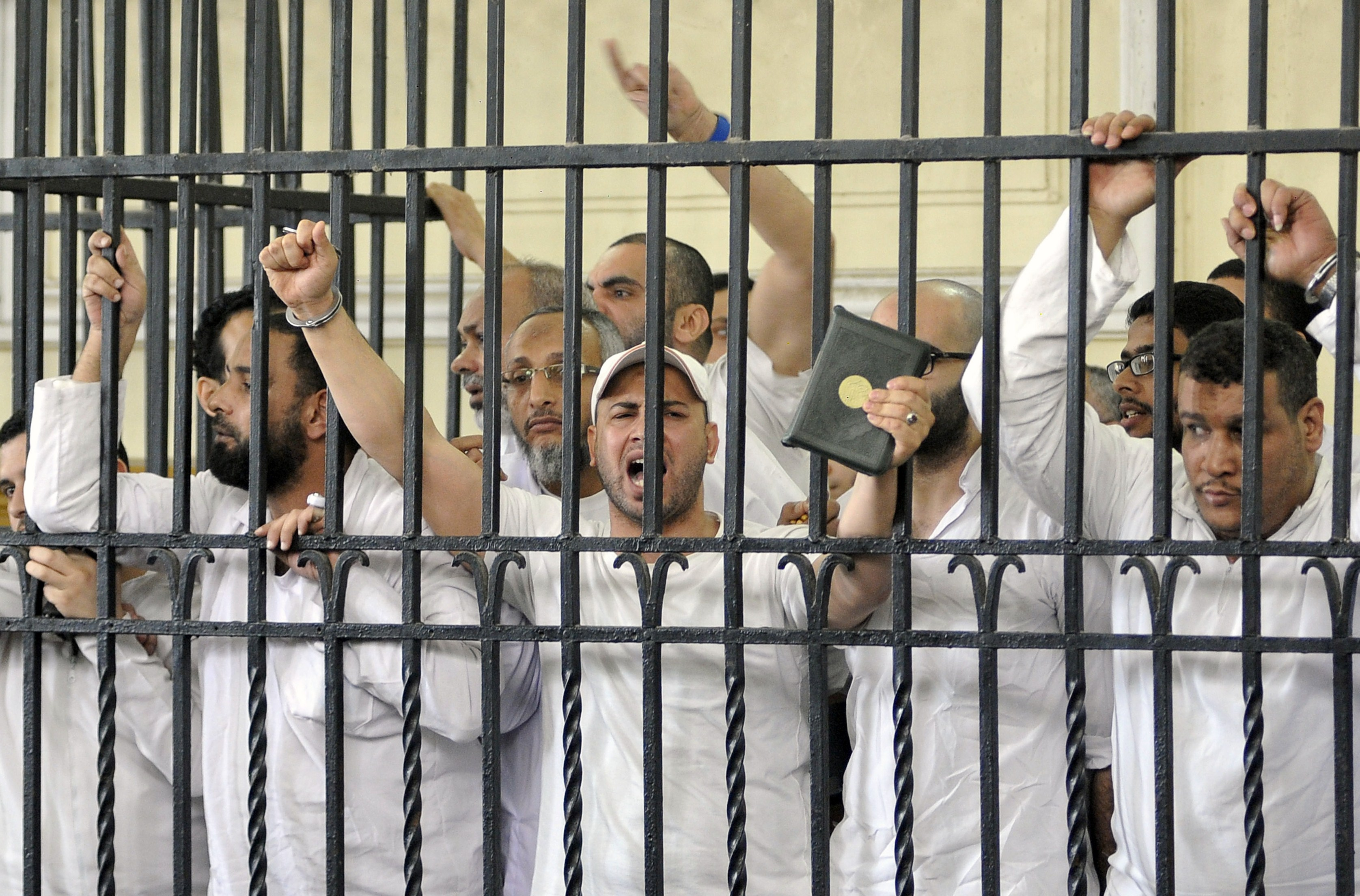 Egyptians react from behind the defendants cage on May 19, 2014 during their trial over deadly violence in the Sidi Gaber neighbourhood of the northern port city of Alexandria on July 5 last year, two days after the army overthrew Egypt's ousted Islamist president Mohamed Morsi. Earlier in the year a court sentenced to death two men for throwing youths off an apartment block roof, one of whom died, during the violence that broke out when supporters and opponents of Morsi took to the streets of Egypt's second city, with one group demanding his reinstatement and the other celebrating the end of his sole year in power.  (AFP PHOTO / STR)