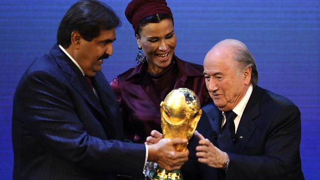 FIFA president Sepp Blatter hands over the World Cup trophy to the emir of Qatar Sheikh Hamad bin Khalifa al-Thani and his wife Chair in Zurich.  (AFP File Photo)
