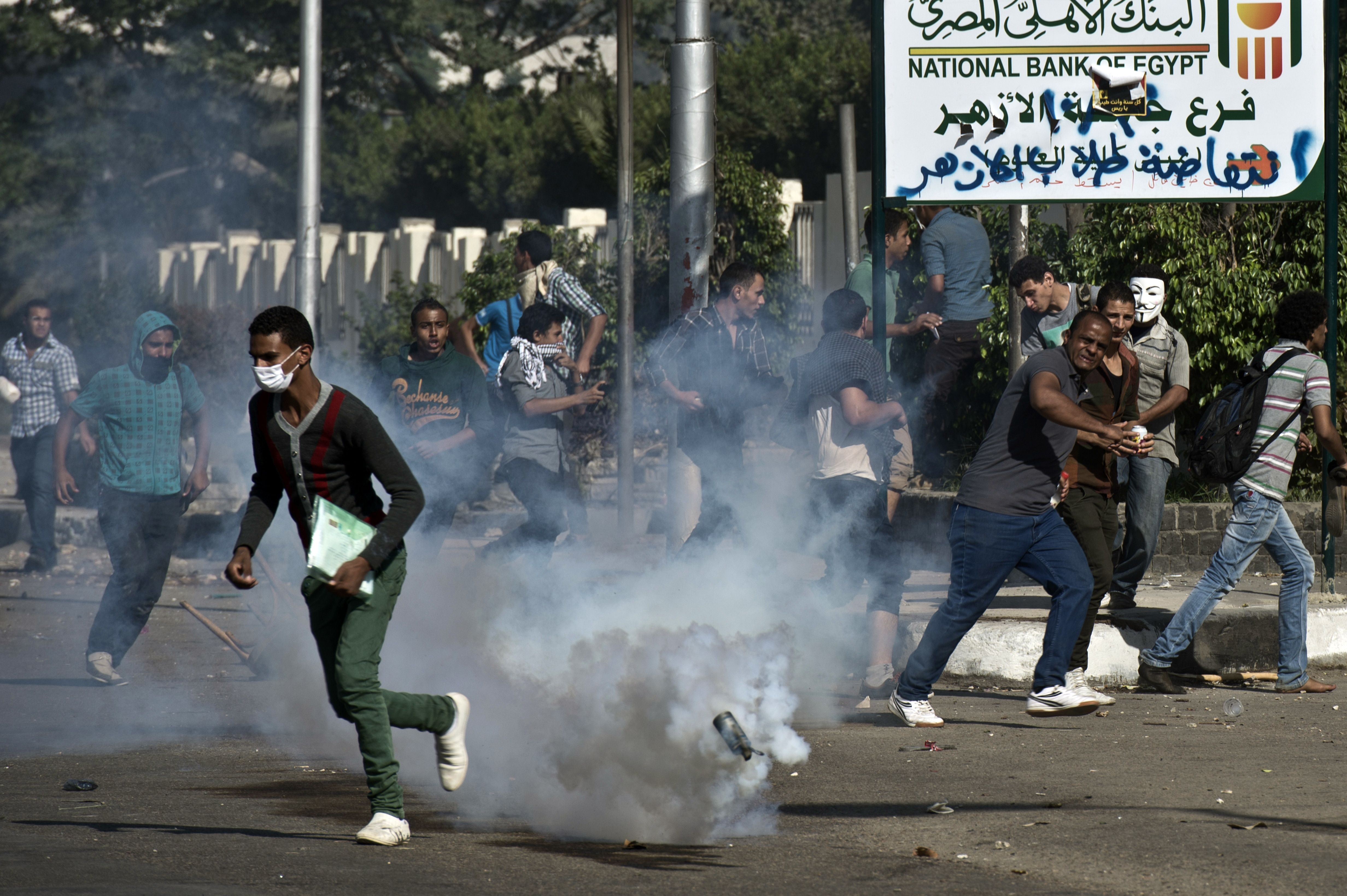 Egyptian students of al-Azhar university run for cover from a tear gas canister fired by riot police during clashes  outside their university campus in Cairo on October 20, 2013 following an anti-army protest. (AFP PHOTO / KHALED DESOUKI)